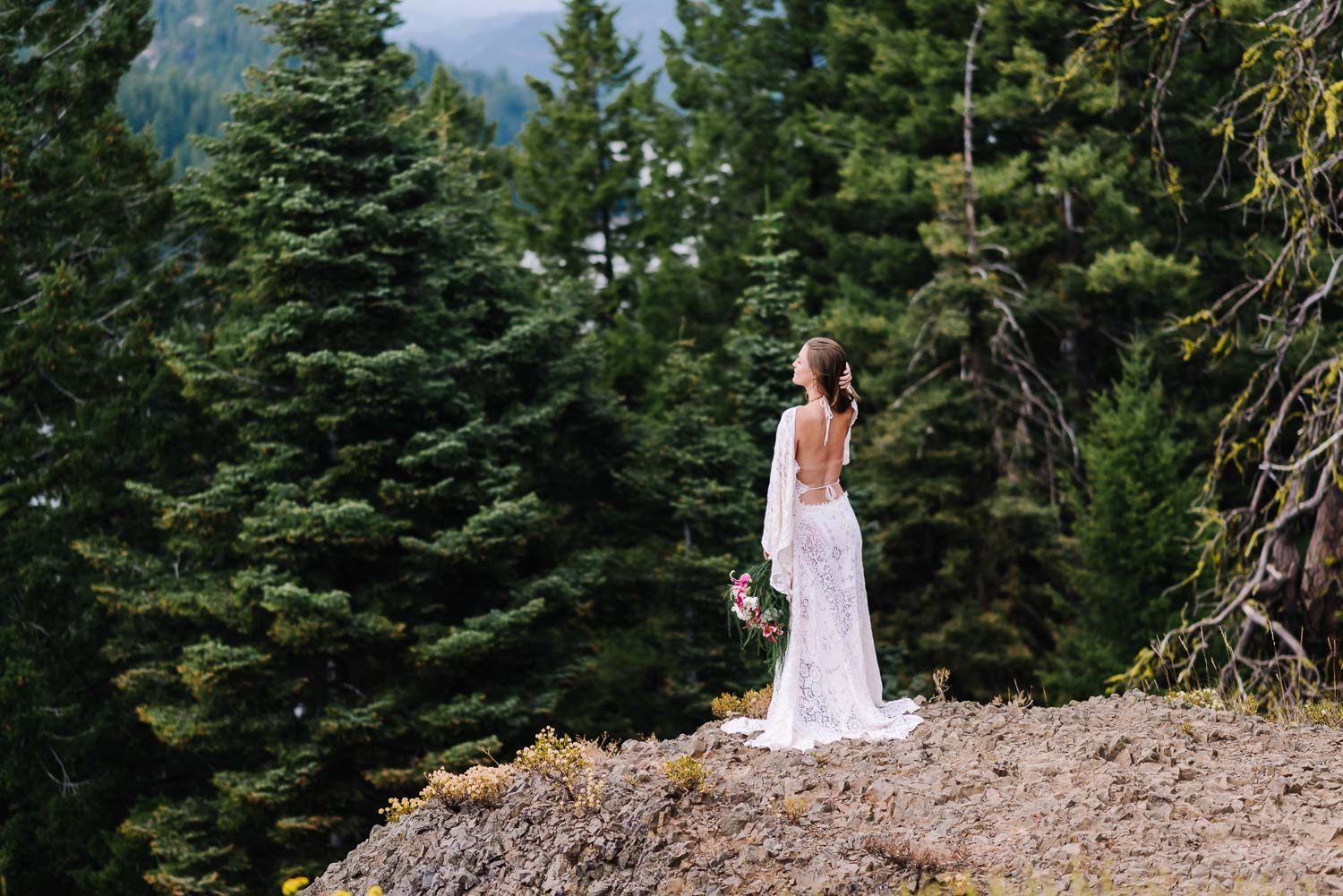 Ponderosa State Park is an adventurous wedding venue in McCall Idaho. Bride standing on Osprey Point with Pine trees behind her.