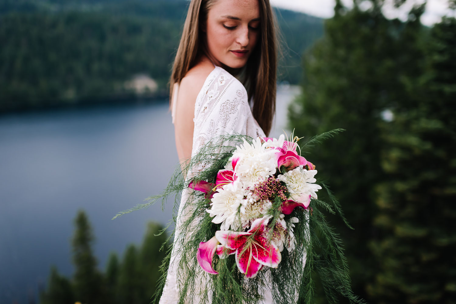 Ponderosa State Park is an adventurous wedding venue in McCall Idaho. Bride standing on Osprey Point holding bouquets with lilies and seeded asparagus.