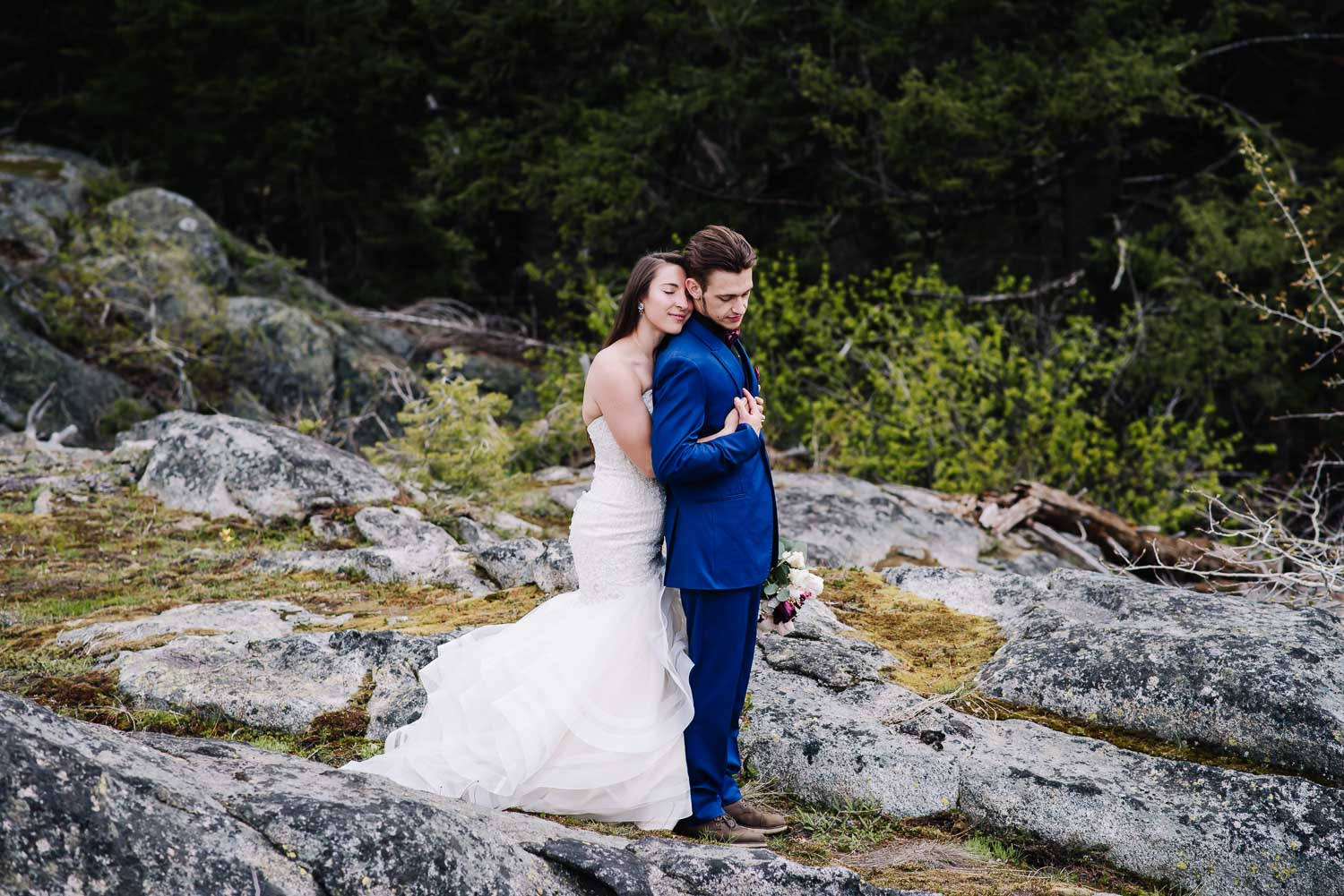 Payette Lake is an adventurous wedding venue in McCall Idaho. Couple standing on rock hugging with pine trees behind them.