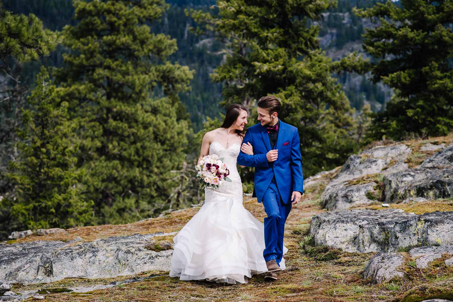 Payette Lake is an adventurous wedding venue in McCall Idaho. Couple walking on rocks with pine trees behind them.