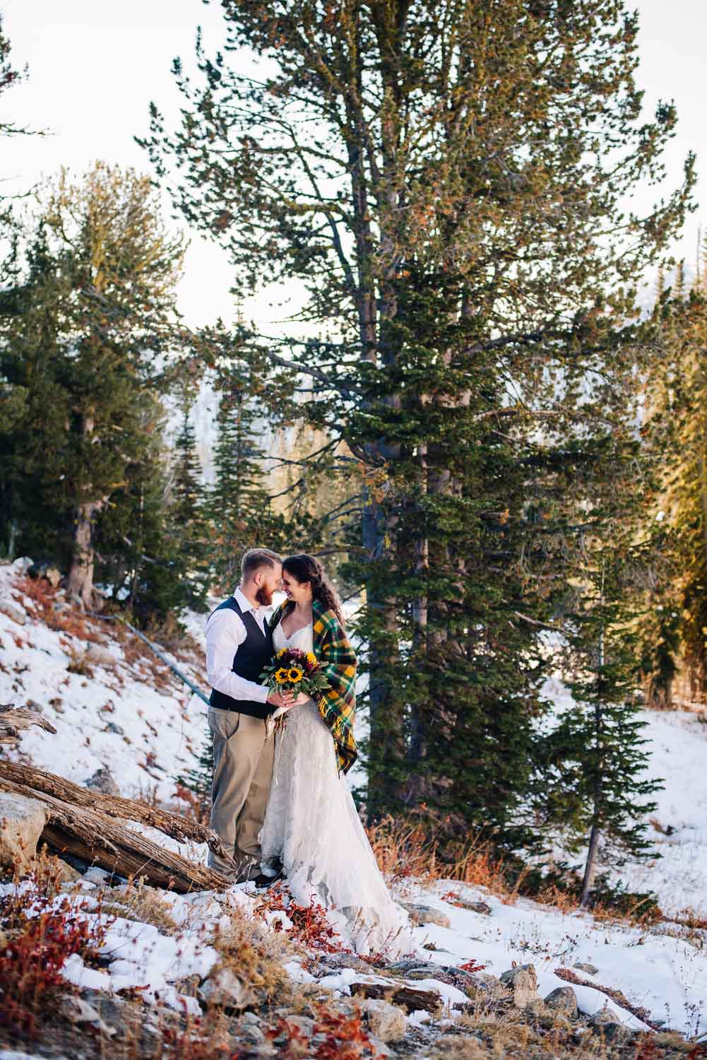 Blue Lake is an adventurous wedding venue in McCall Idaho. Couple standing on rock with pines behind them.