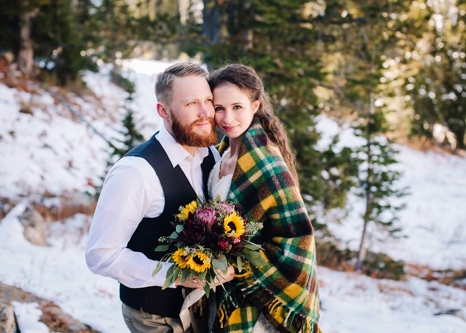 Blue Lake is an adventurous wedding venue in McCall Idaho. Couple standing on rock with pines behind them and sun on their faces.