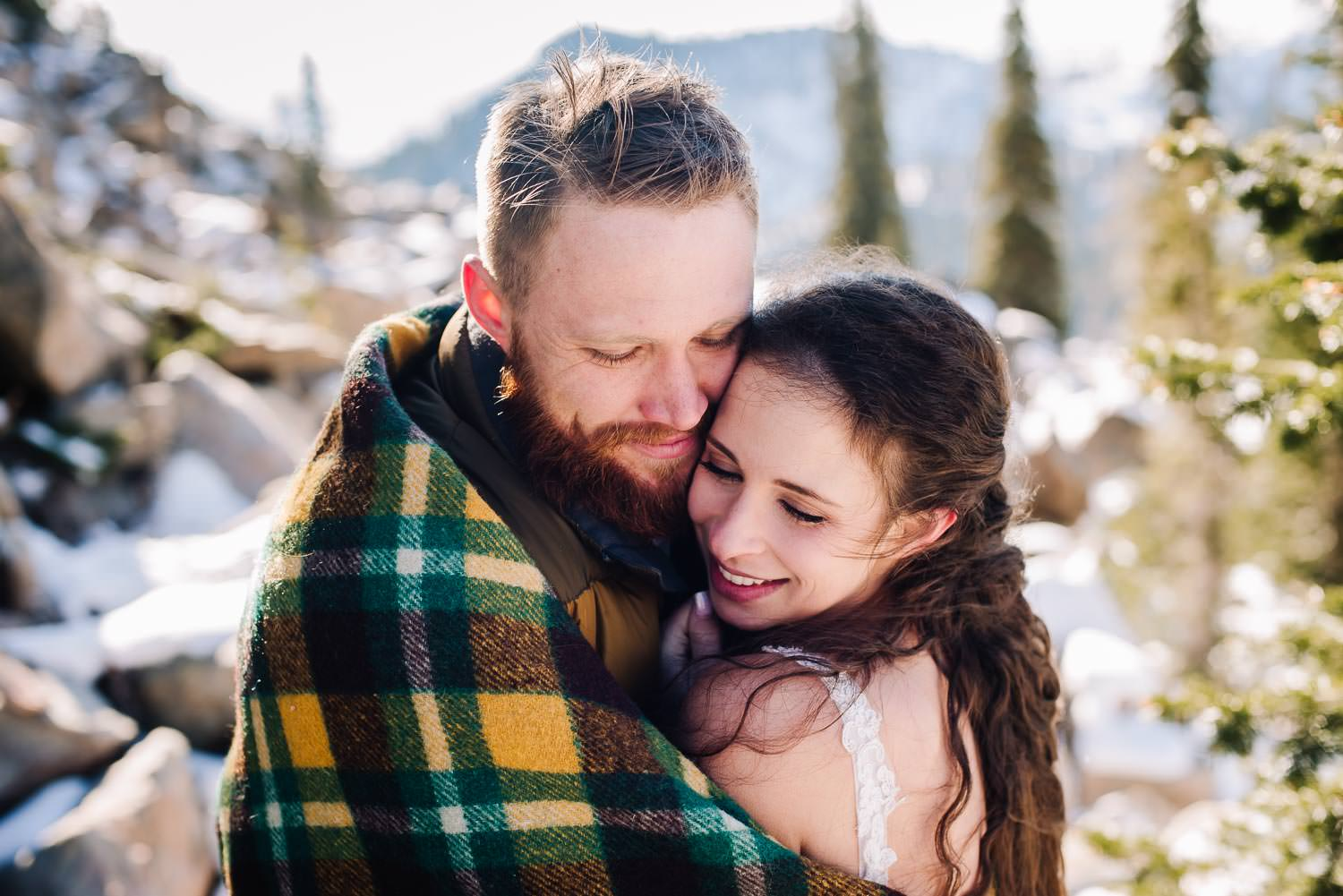 Blue Lake is an adventurous wedding venue in McCall Idaho. Couple hugging in wool blanket with mountains behind them.