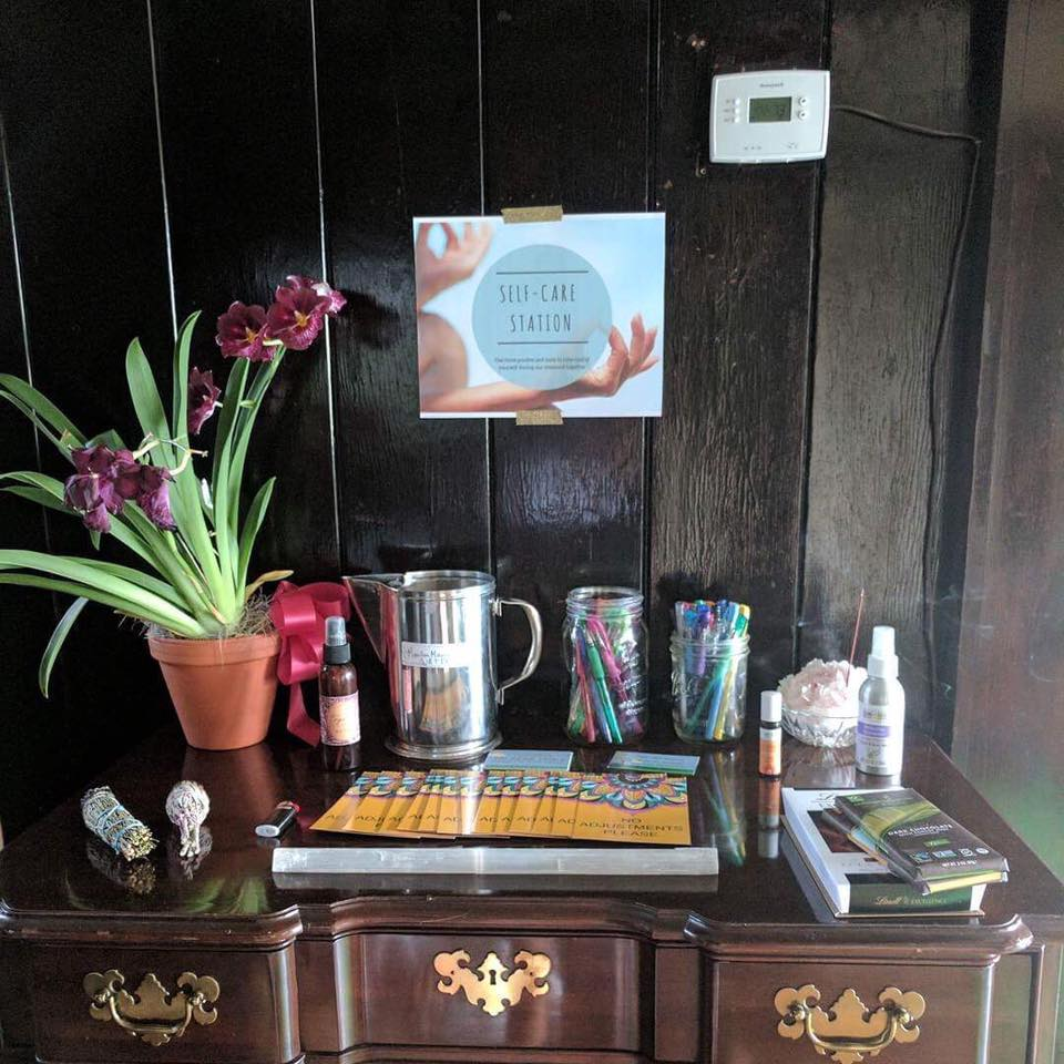 Setting up a Self-Care Station for all of the students to use throughout the weekend: organic dark chocolate, 'No Adjustment' cards, sage, incense, fresh mineral water, sacral chakra essential-oil-blend, lavender spray, rosewater spray, a selenite wand, and an assortment of beautiful flowers.