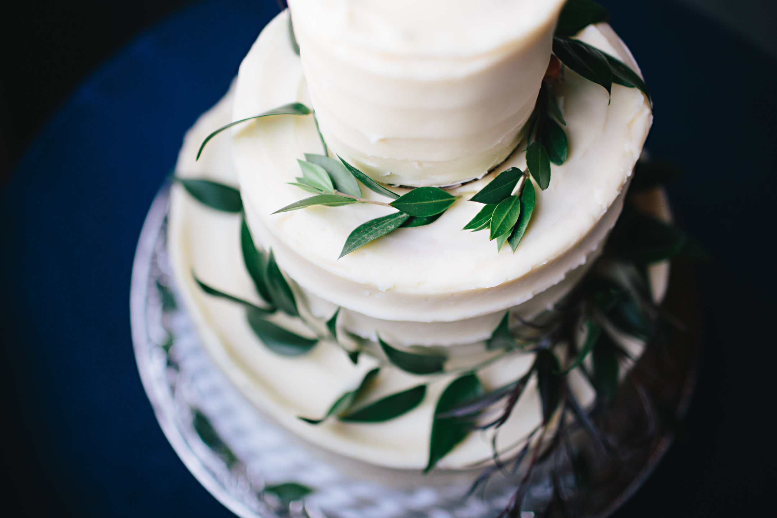 A gorgeous wedding cake decked out in greenery which tied into the simple and elegant centerpieces.