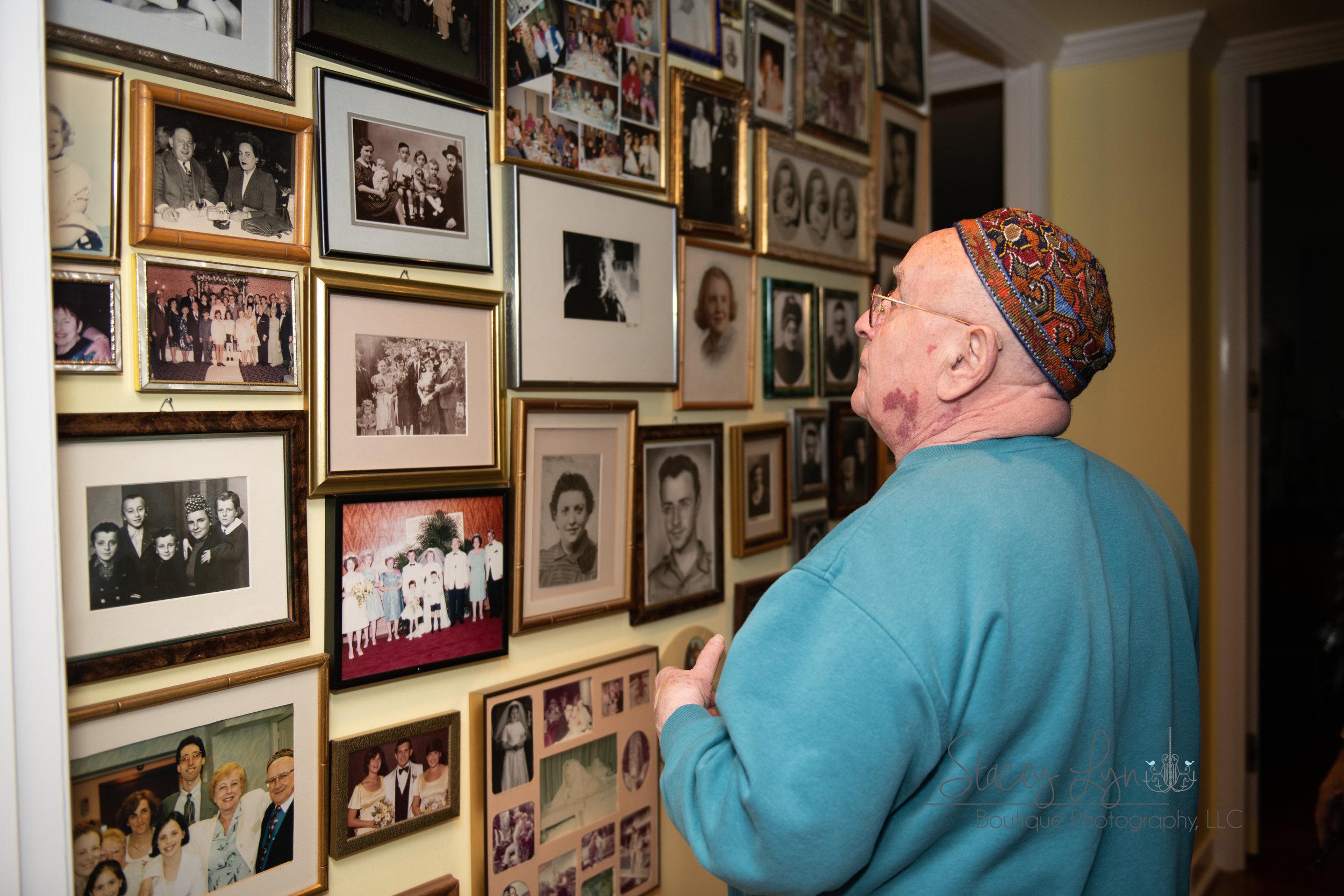 Mr. Judah Samet looking at his wall of family memories