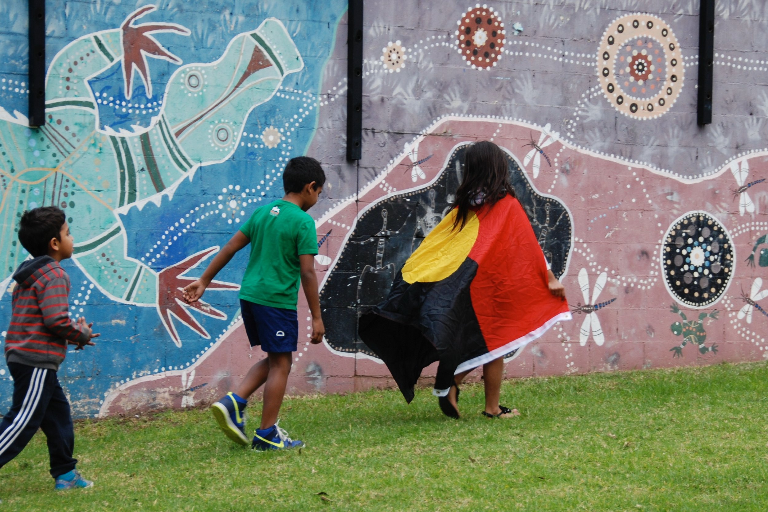 Walking down Eveleigh St in Redfern past the Aboriginal painted mural and wearing the Aboriginal flag