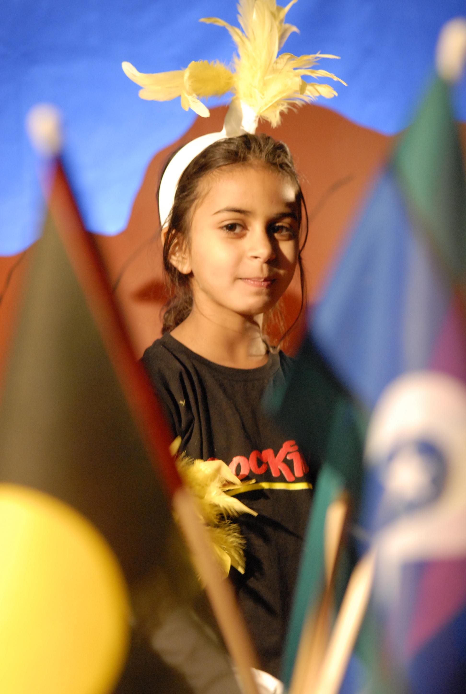 Aboriginal girl standing with Aboriginal flag and the Torres Strait Islander flag. pride in Indigenosu cultures