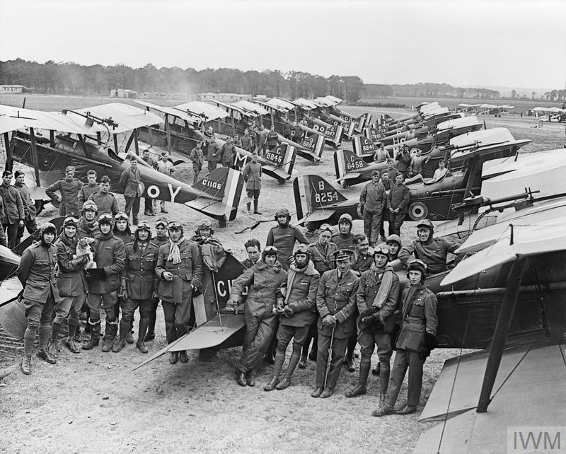 Officers and S.E.5a Scouts of No. 1 Squadron, RAF at Clairmarais aerodrome near Ypres. The group includes two Americans serving with the Royal Air Force, Lieutenants D. Knight (extreme left) and H. A. Kuhlberg (extreme right). © IWM (Q 12063)