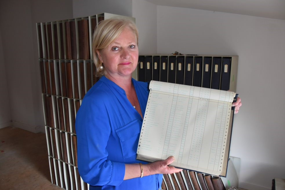 Christine holding an index of WWII (at the top, details of two soldiers carrying her Christian name 'KETELS') and behind the WWI records.