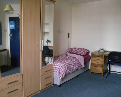 Twin room containing two single beds, two desks, two wardrobes, a vanity unit and a fridge.