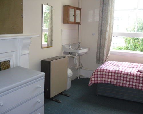 Large single room overlooking the garden. The room contains a single bed, a desk, a wardrobe a vanity unit and a fridge.