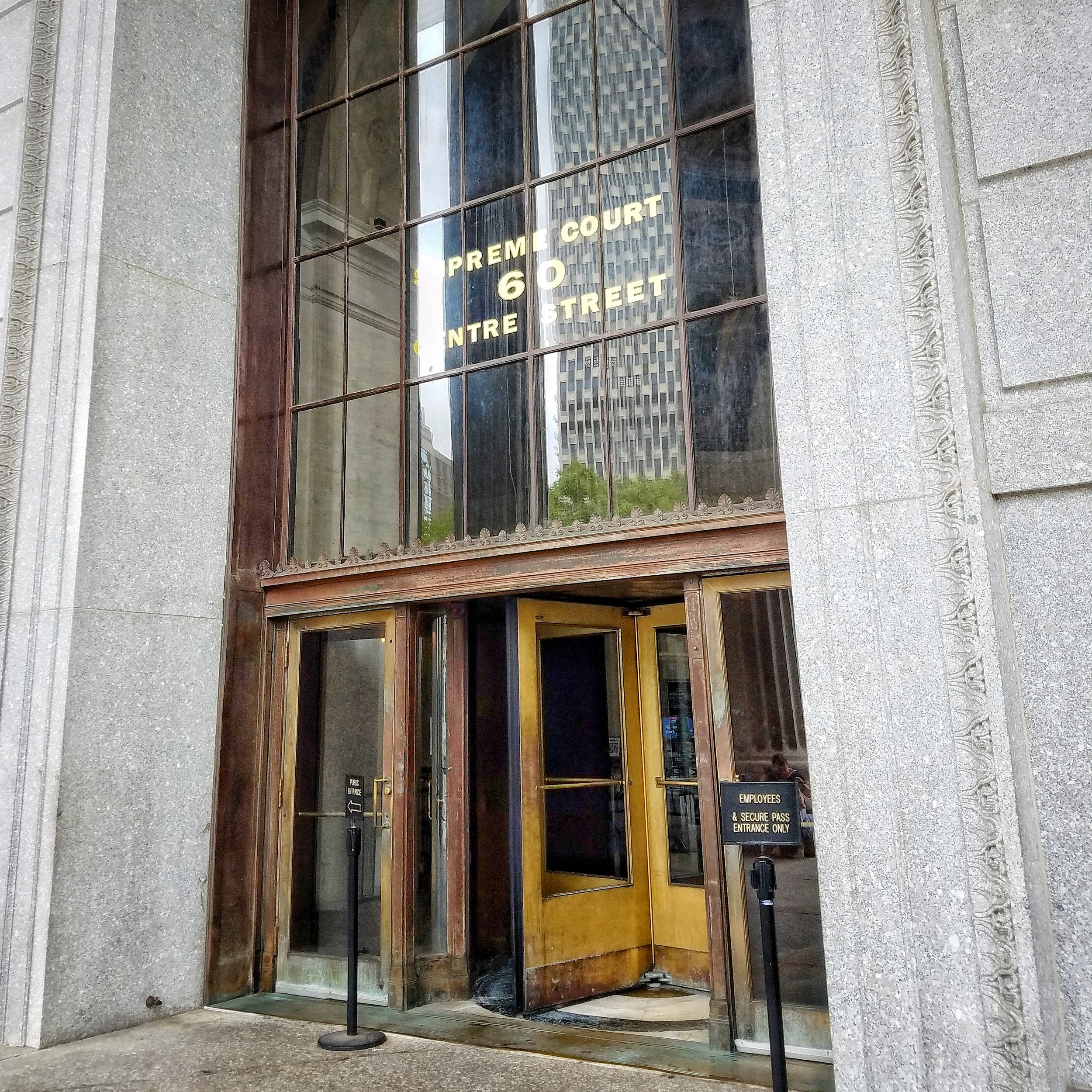"""The entrance to 60 Centre shows the building's address in the windows (""""Supreme Court 60 Centre Street""""). There is a wooden revolving door in the center and two regular doors on either side. The regular door on the right is reserved for employees."""