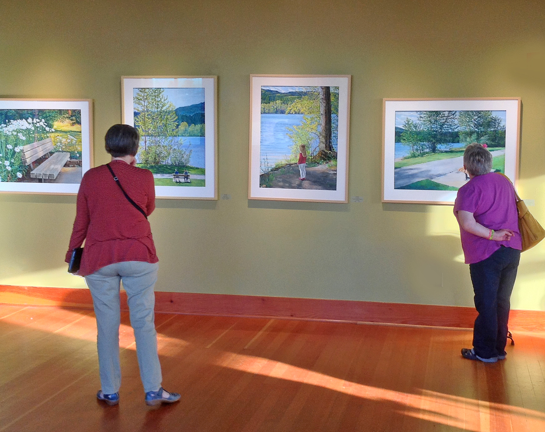 LOOKING AT PAINTINGS.  AN ART EXHIBIT AT THE JANSEN ART CENTER IN LYNDEN, WA