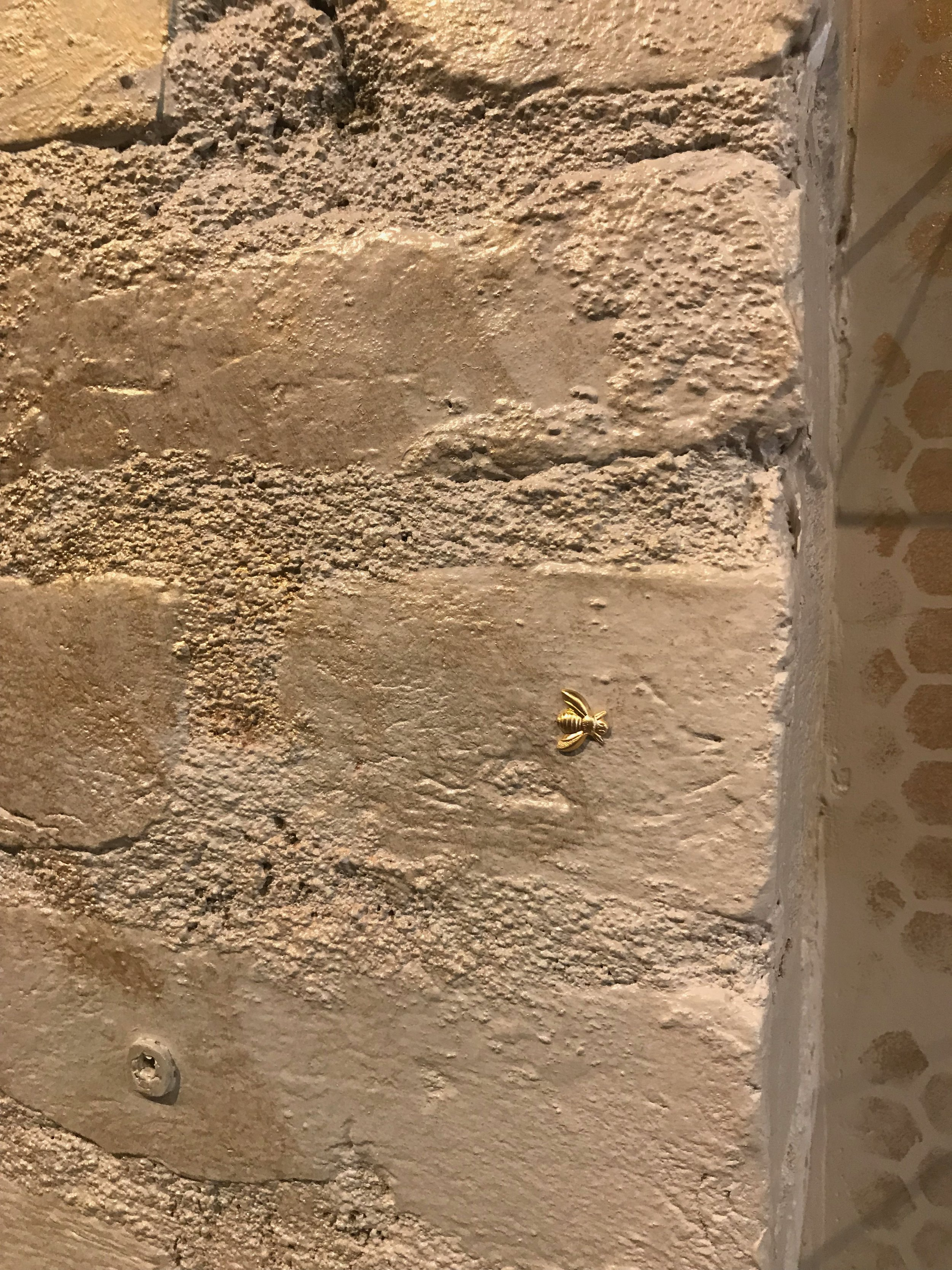 Hidden treasures, like these tiny gold bees embedded in the wall, reward visitors for taking a moment to appreciate life's small joys.