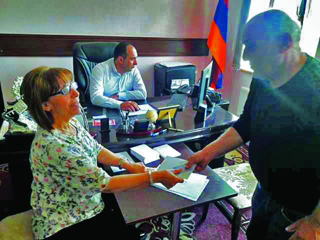 Gayane Muradyan, Tekeyan Cultural Association Yerevan office director, handing a gift to one of the staff at the Vahan Tekeyan School in Stepanavan, Armenia, 2018