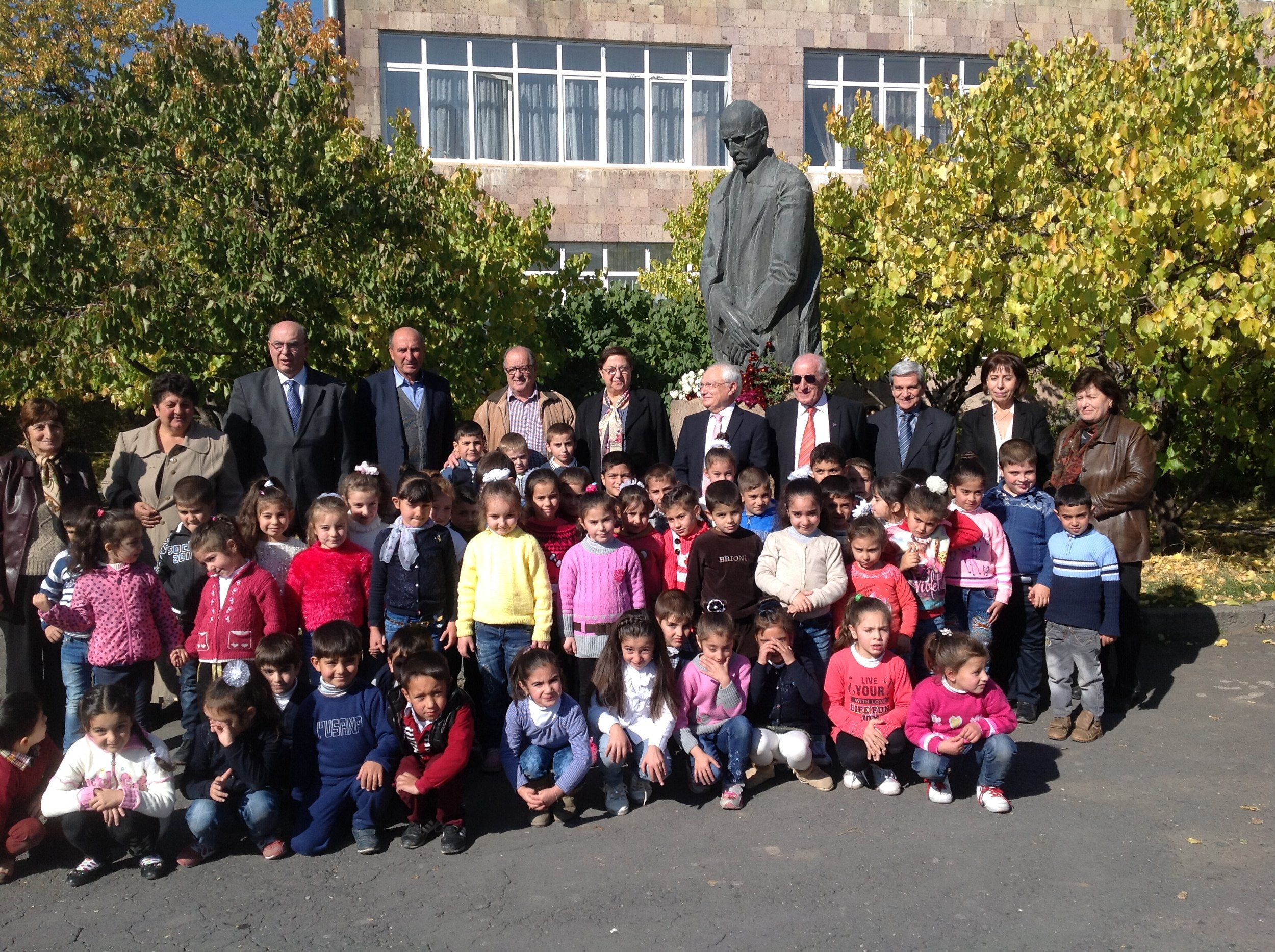 A delegation of Tekeyan Cultural Association leaders visit the Vahan Tekeyan School in Karbi, with the statue of Tekeyan in the background.