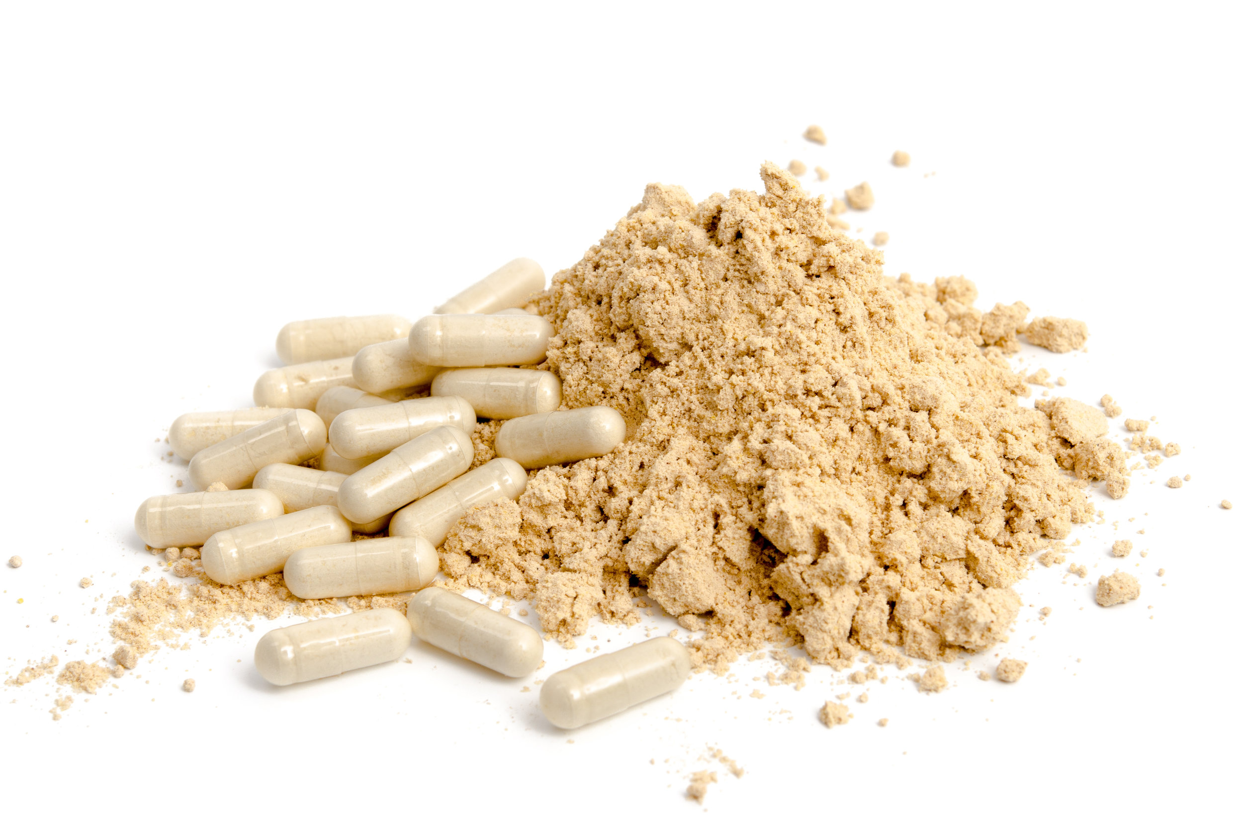 Pile of tan powder and powder in nutraceutical capsules