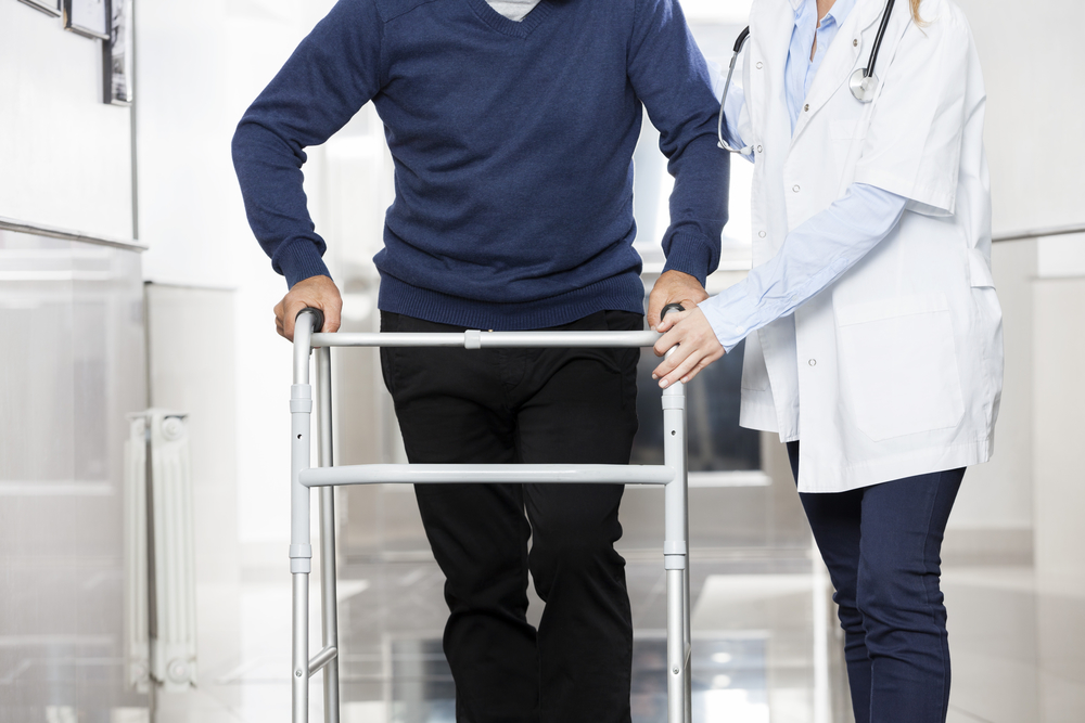 Midsection Of Doctor Assisting Senior Man With Walker