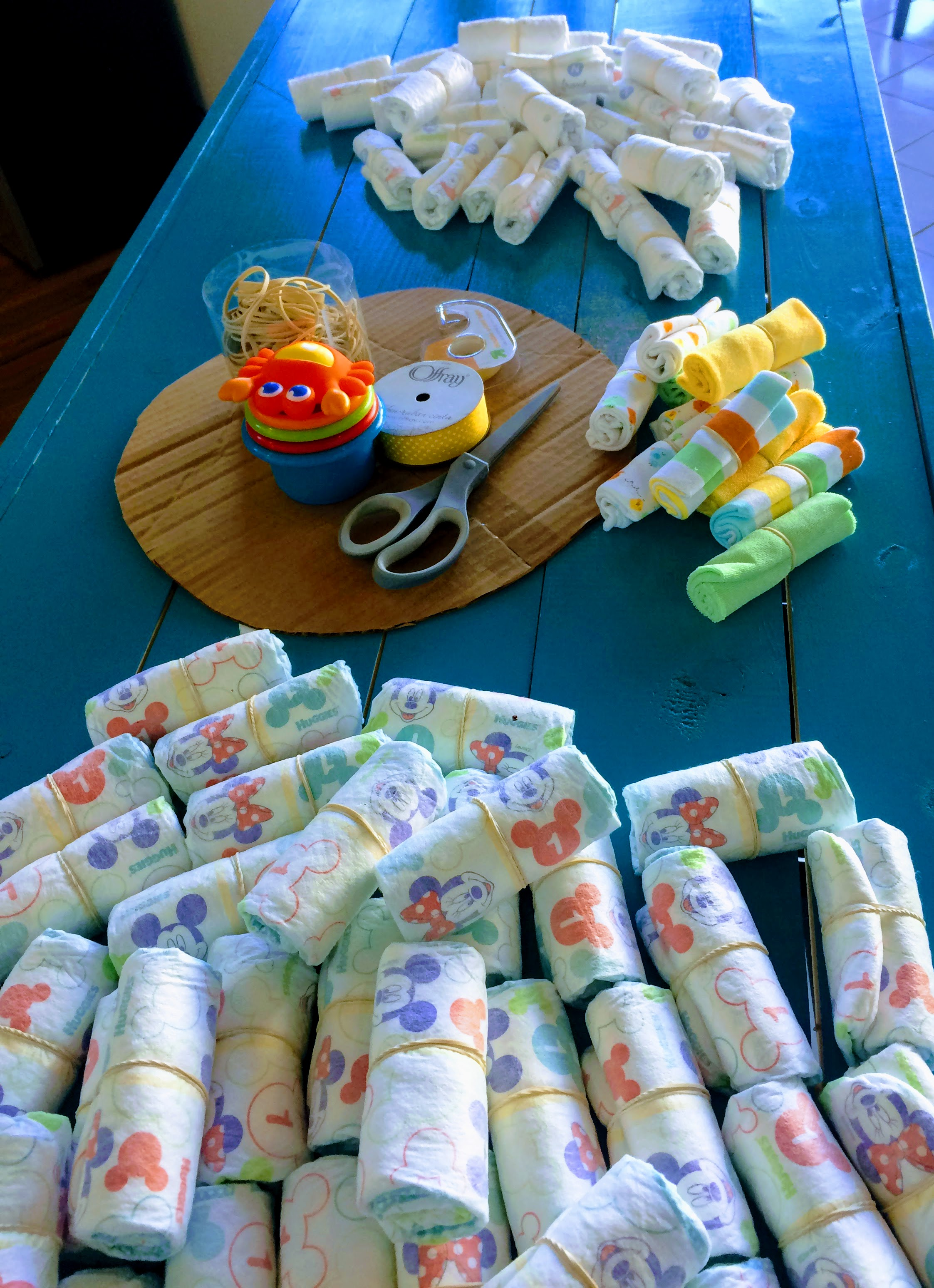 Now you're ready to get started! Roll all of your diapers (and other 'cake' materials) up, starting with the open end of the diaper. Secure each around the middle with a rubber band. It helps if you place the rubber band in close to the same spot on each diaper, so you can easily cover them up with ribbon later. Some diapers have a yellow line down the middle as a wetness indicator, and this can be very useful when attempting to position the band in the same spot.