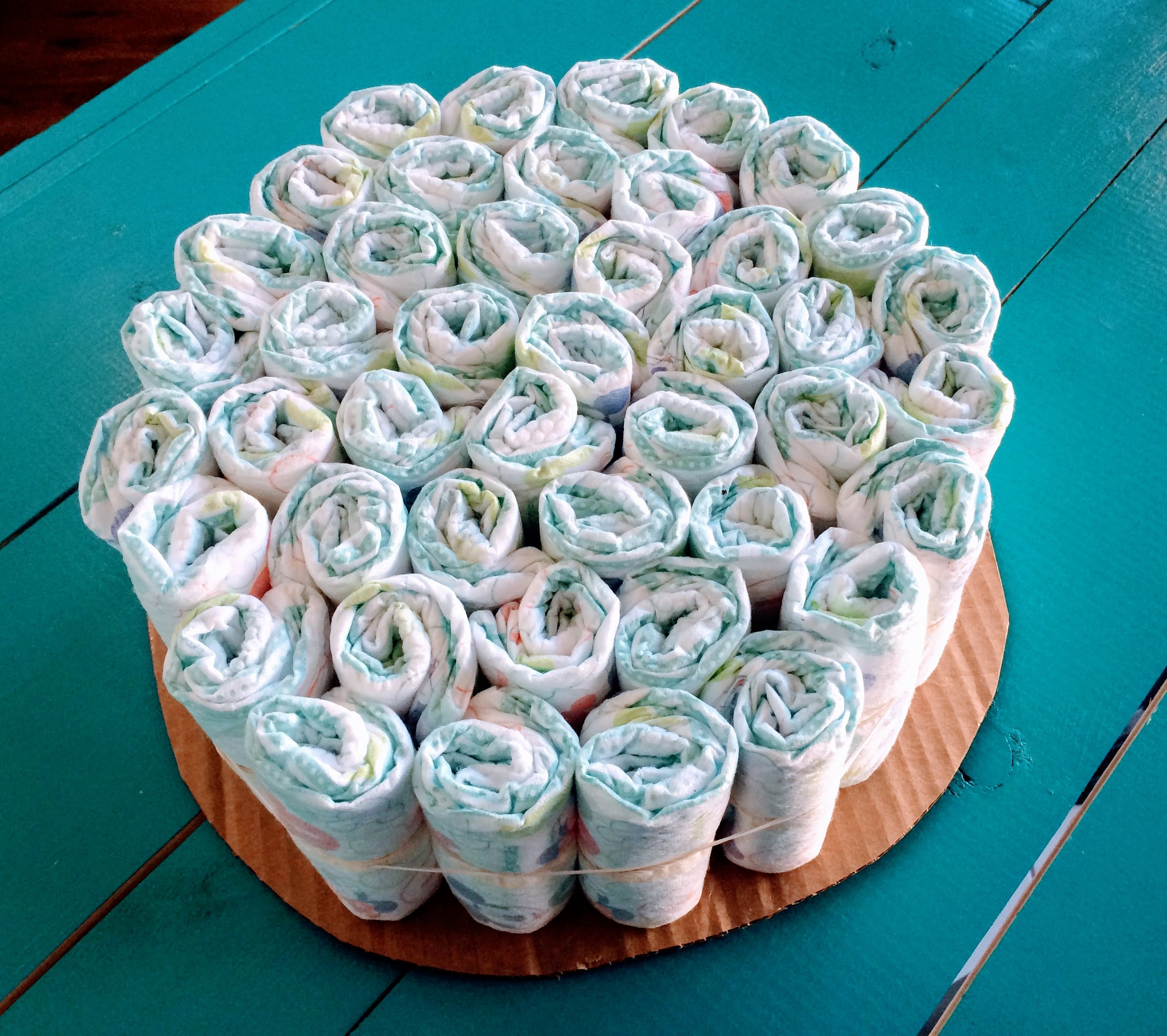 Next, gather all of your biggest diaper size together to form the bottom cake layer. You'll need a large rubber band for this part. If you have a helper, have them hold as many as possible while you set the rubber band around them. If you're doing it solo, just put as many as you can inside the rubber band to start, and continue adding around the outside, Rubber bands are stretchy - don't worry!