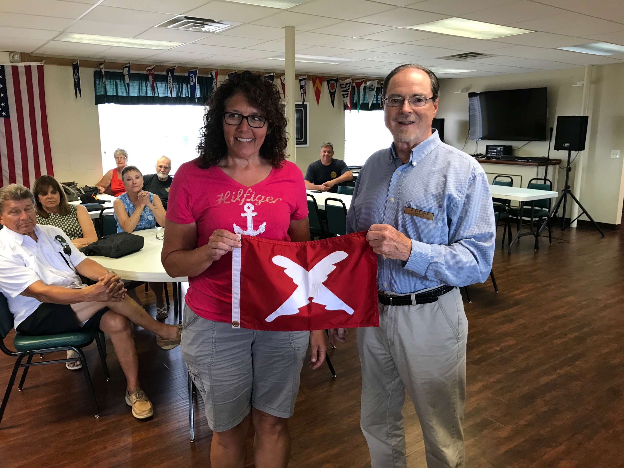 Commodore Harvey Rickert recently presented Brenda Marcks her Membership Committee flag.