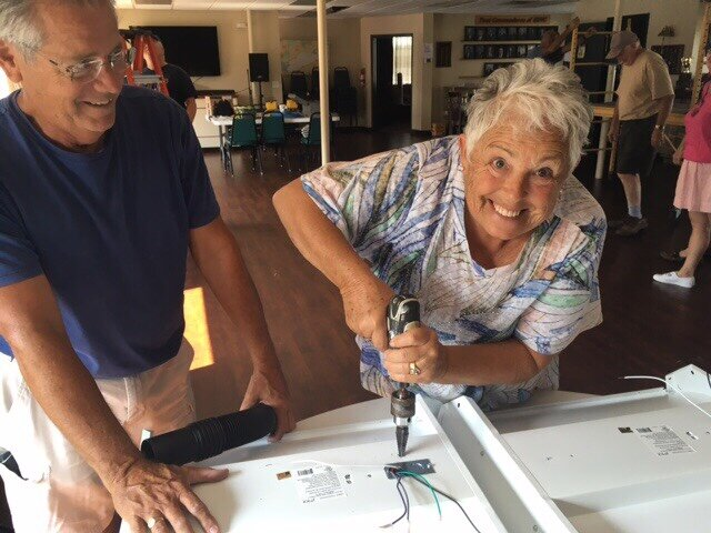 John Hukill and Susan Young getting light fixtures drilled and wiring for installation (HBYC's Susan the Riveter)