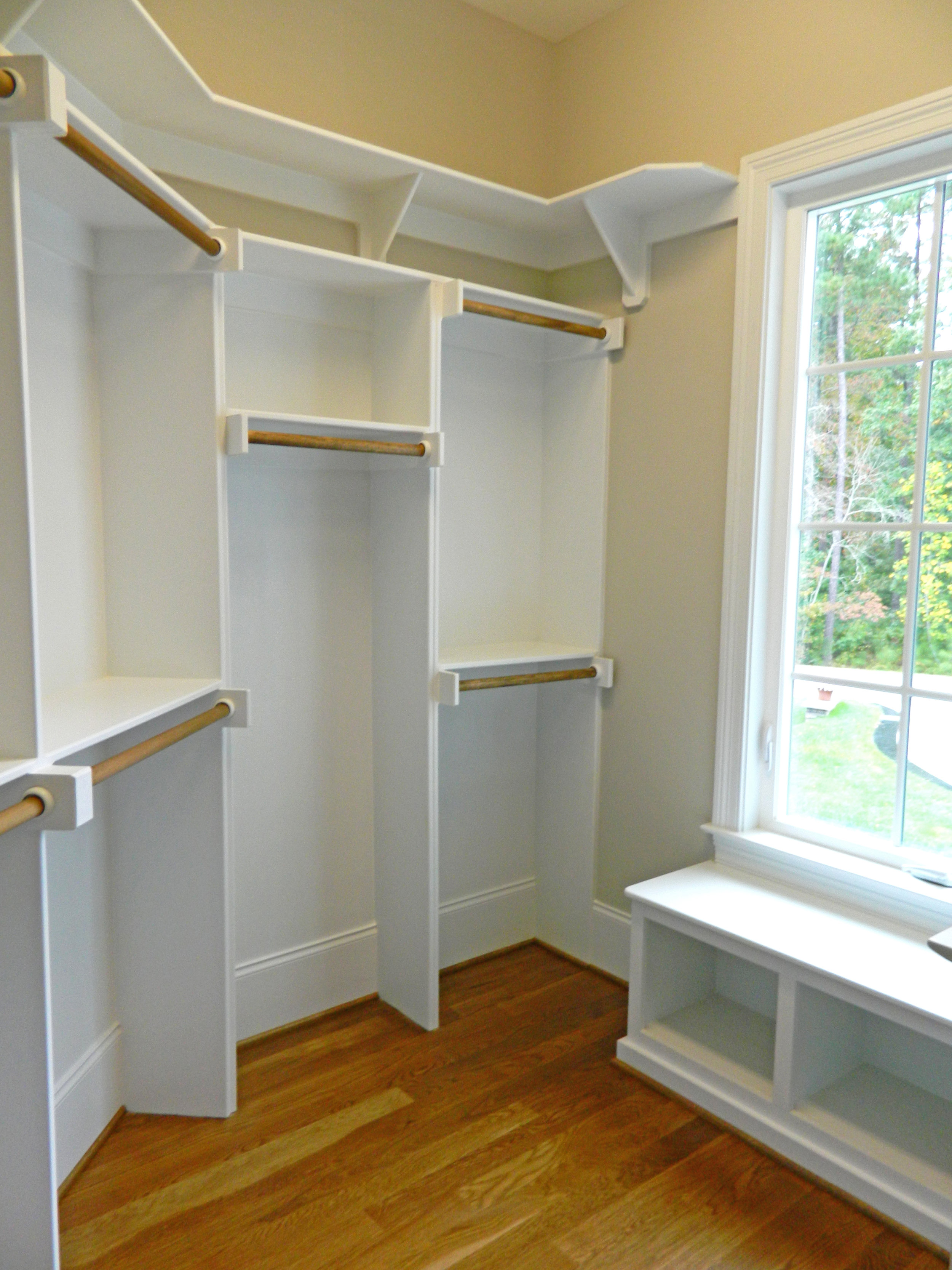Walk-In Closet with Window Seat, Double & Long Hang, and Cleated Shelf at Top