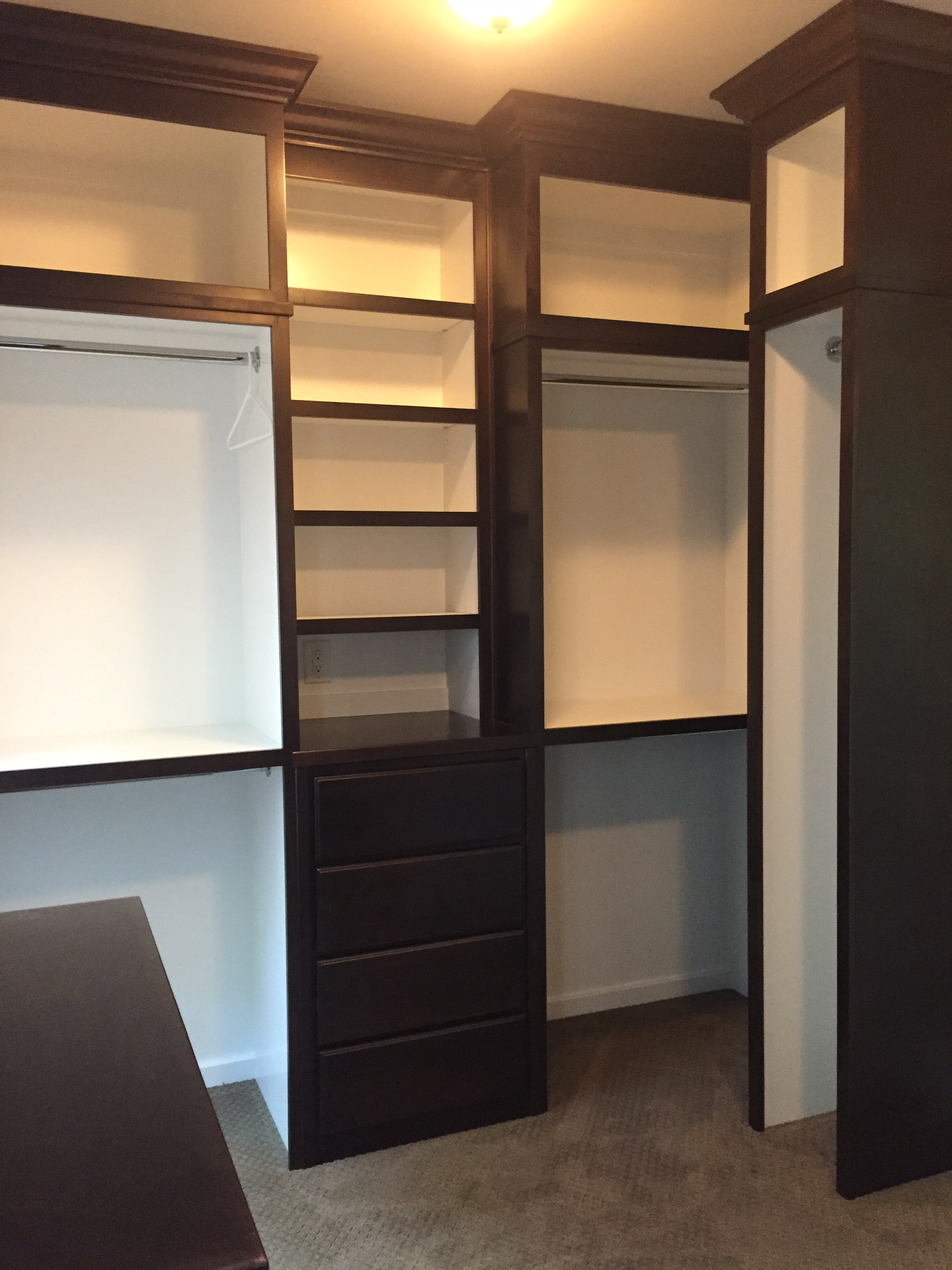Stained Master Closet with Painted Interior, Open Cubbies, Hanging with Shelf Above, and Island with Slab Drawers