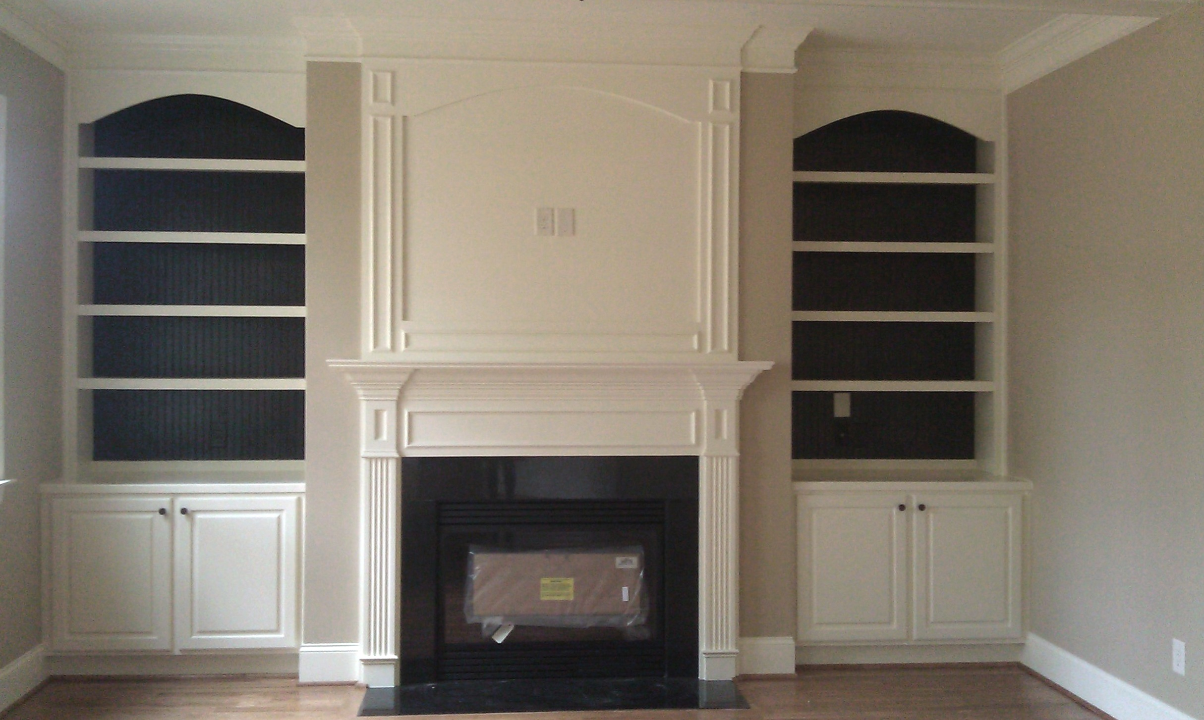 Fireplace Built-Ins with Adjustable Shelves, Arch Detail, Accent Backer Color, Raised Panel Doors, and Crown