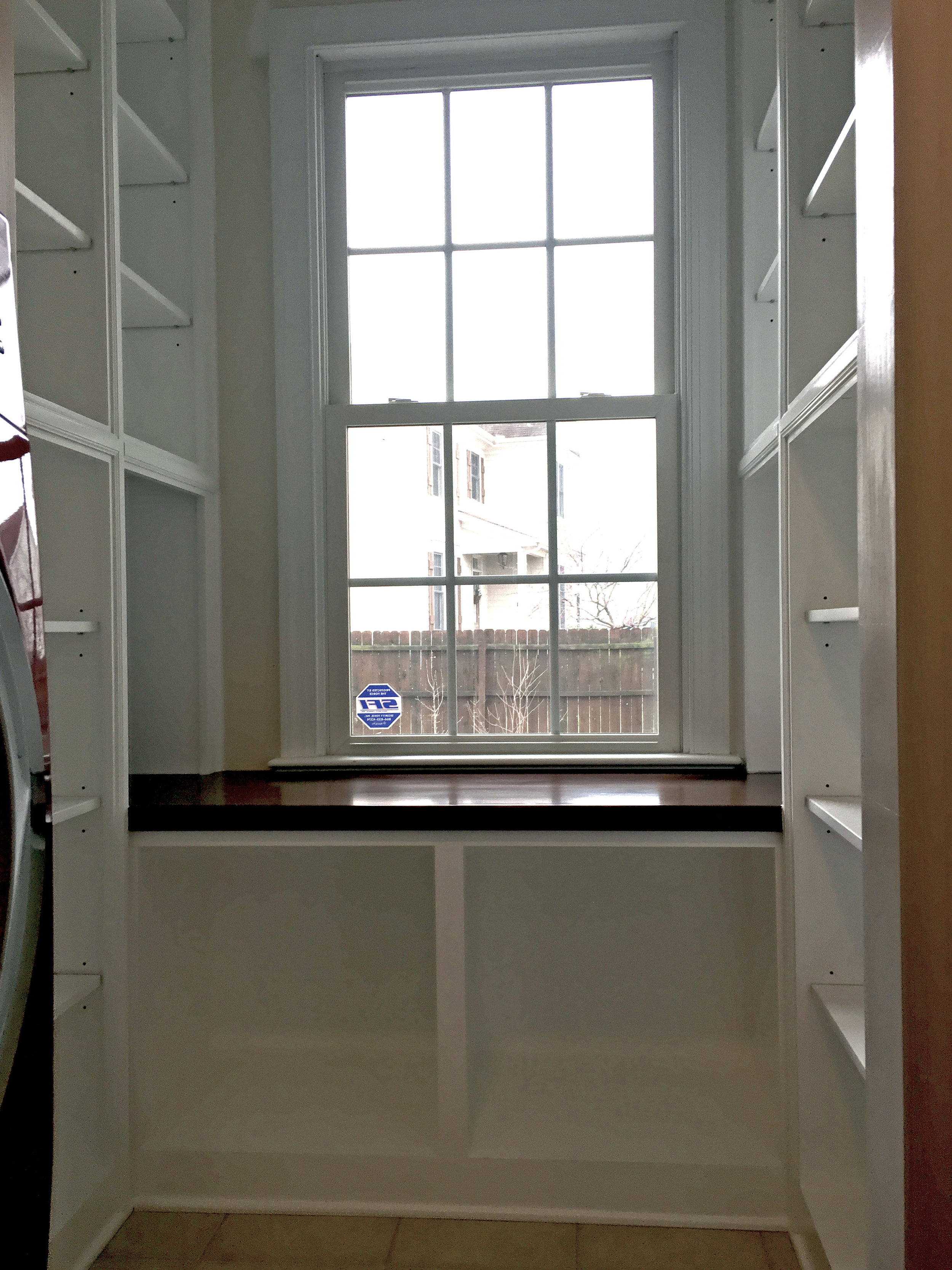 Custom U-Shaped Pantry with Window Seat, Adjustable Shelves, and Crown