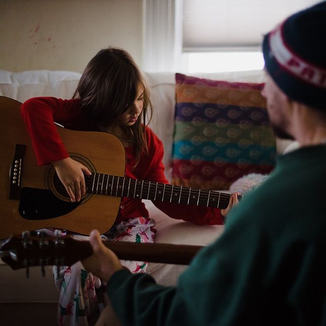 He demonstrates and teaches and encourages her to try again and practice.  She stretches her fingers to reach strings and grins up at him when she gets it right, and they dance back and forth in this space of learning and playing and connecting across chords and melodies.