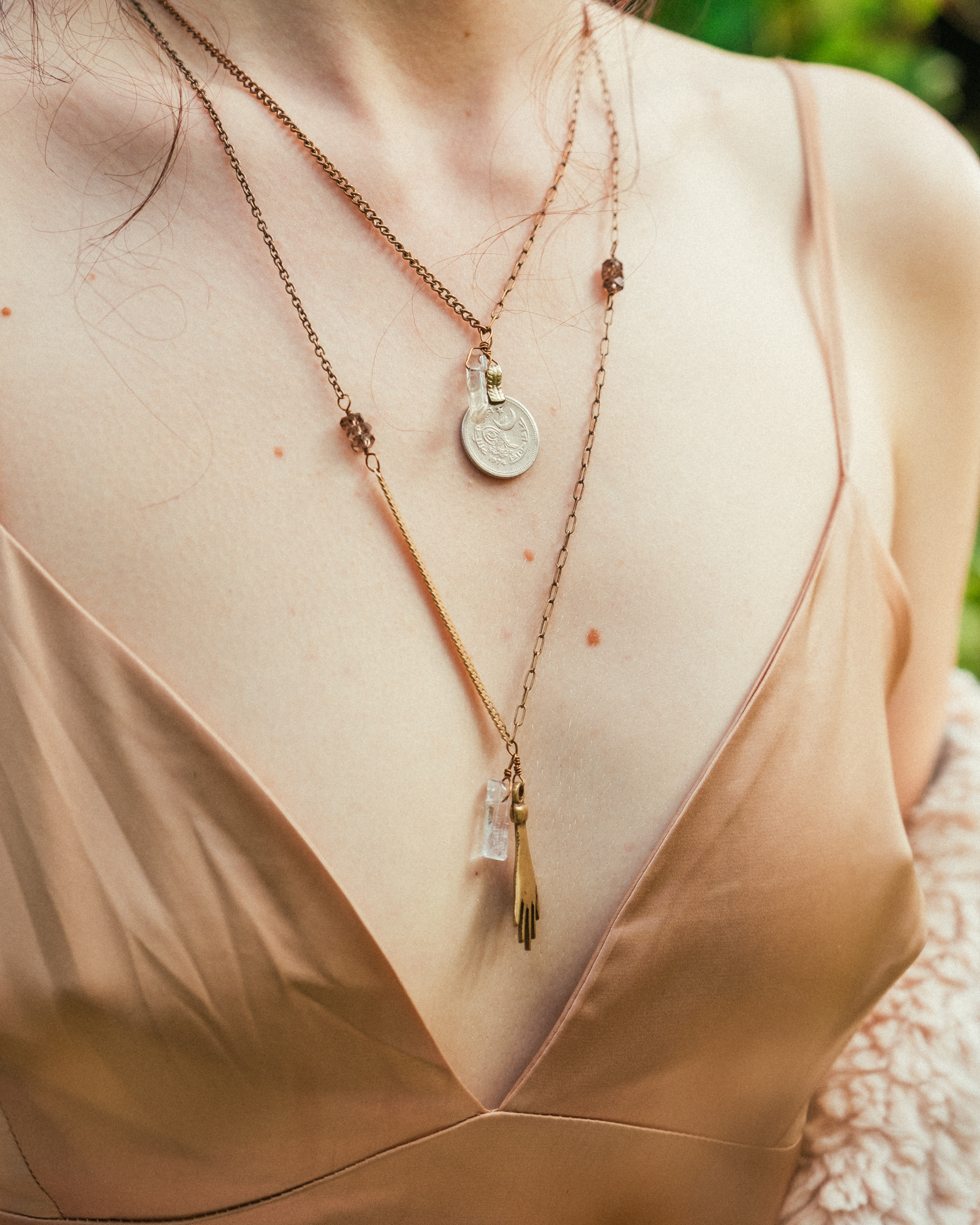 Vintage coin & crystal necklace on brass. Paired with Frida long necklace on wire wrapped smokey quartz beads, 14kt gold, and brass. Photo by Richard Fusillo.