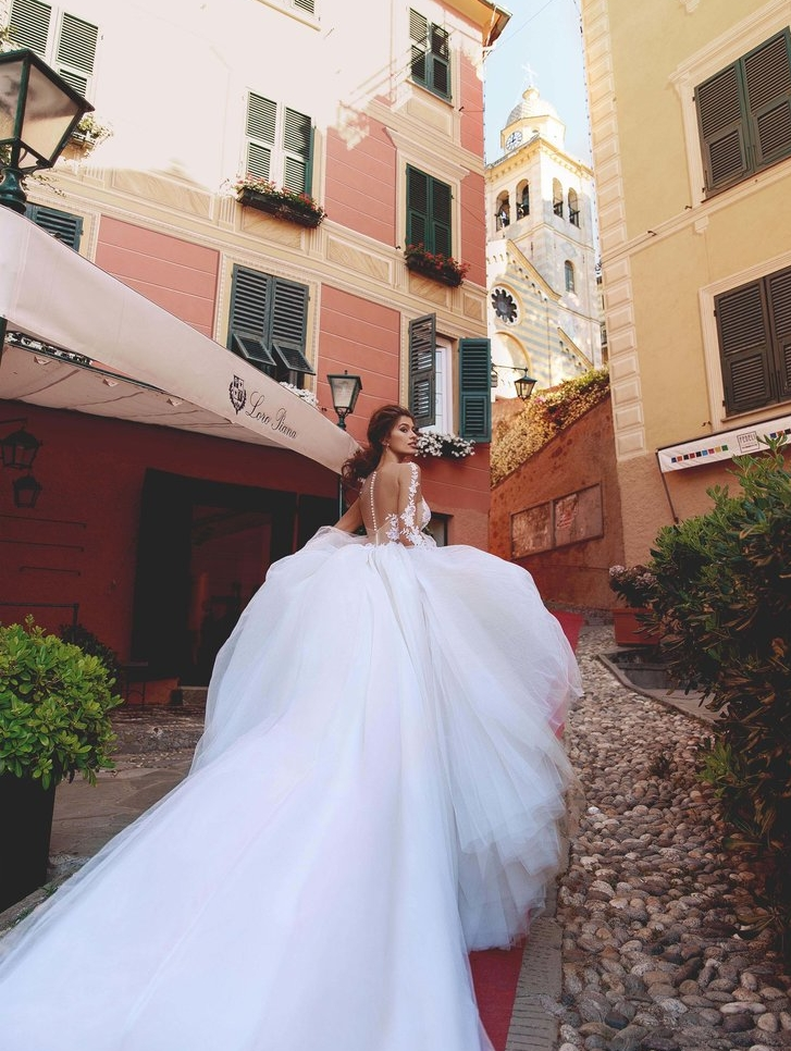 This angelic, long-sleeved ball gown dazzles in the sun and shimmers at night.