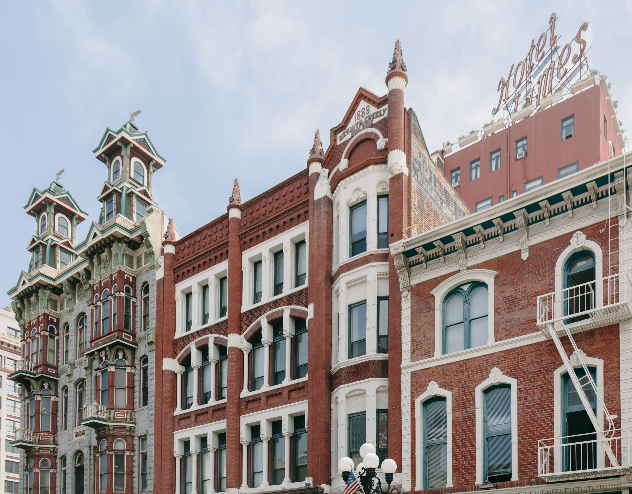 Left: Louis Bank of Commerce in the Baroque Revival Style (1888), which once housed an oyster bar frequented by Wyatt Earp.Right: NeSmith-Greeley Building in the Romanesque Revival Style (1888). The sign for the historic Hotel St. James (1913) can be seen in the background.