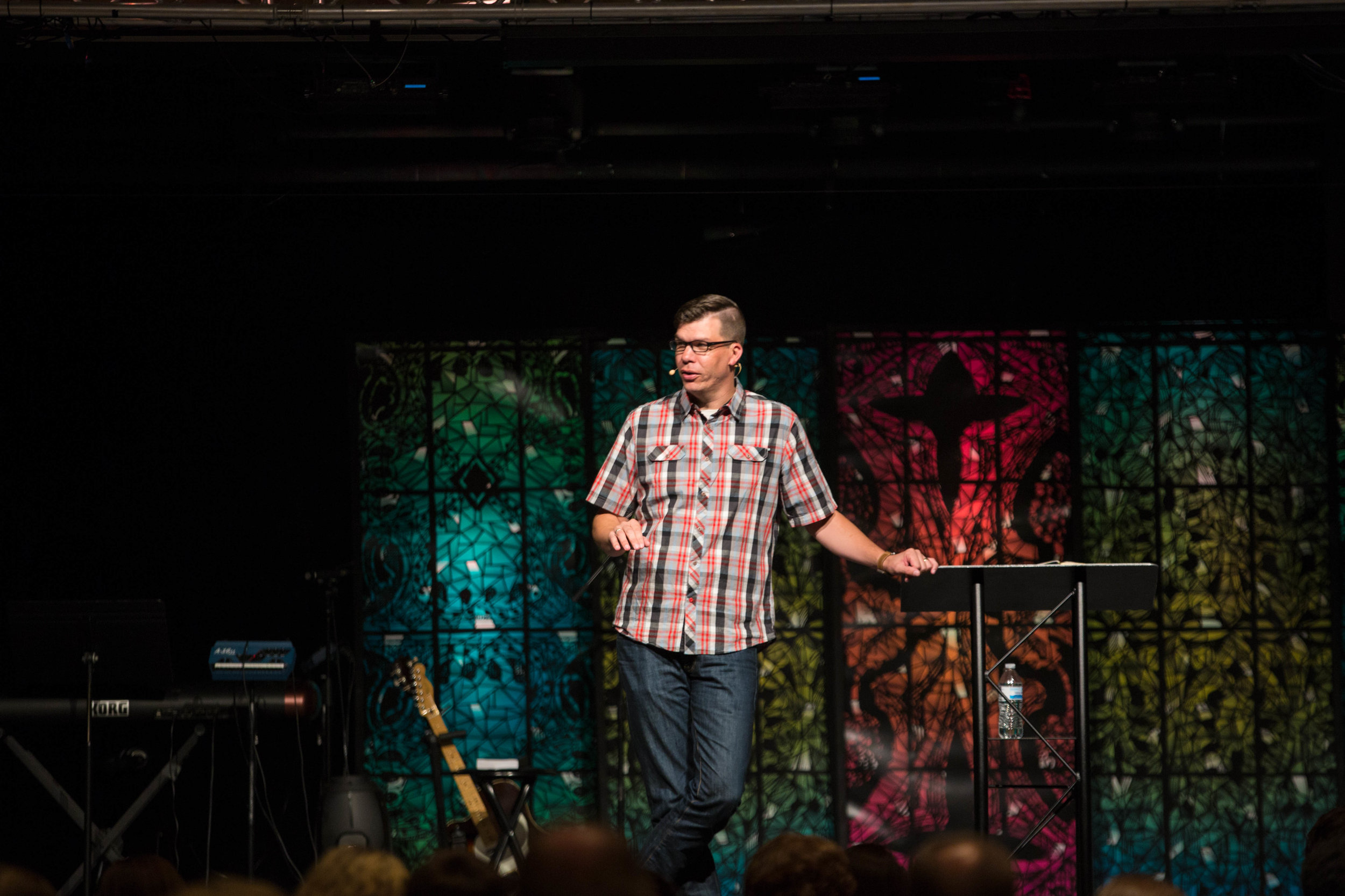 Pastor Micah preaching in front of stained glass stage design.
