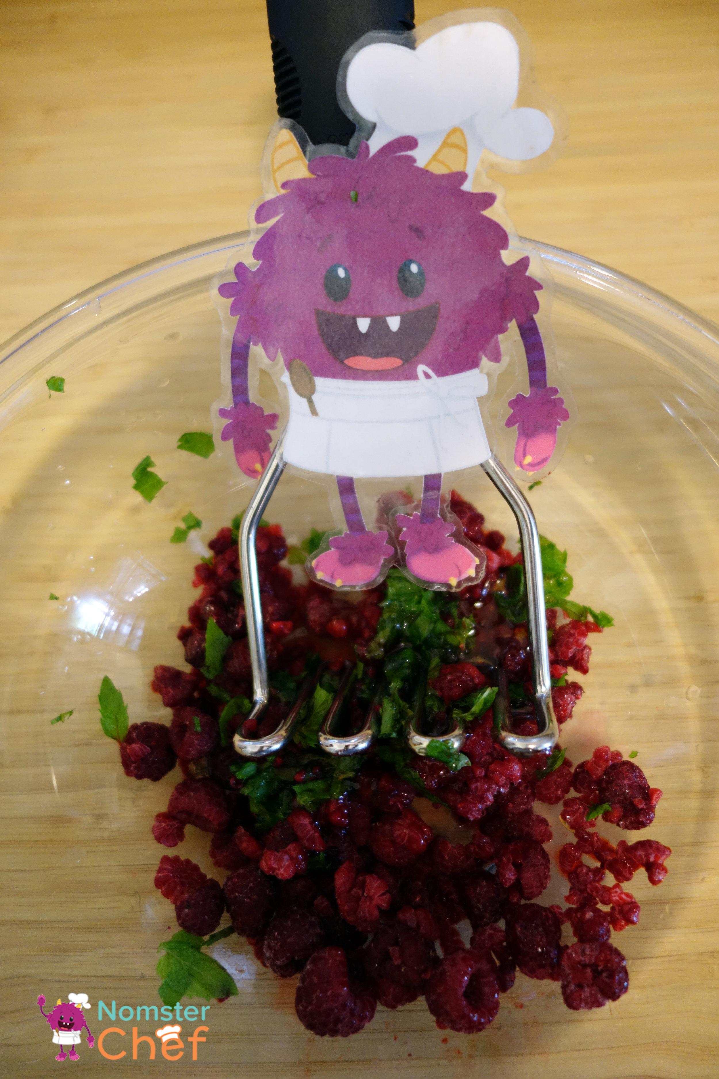 mashing raspberries - raspberry yogurt pop- Nomster Chef