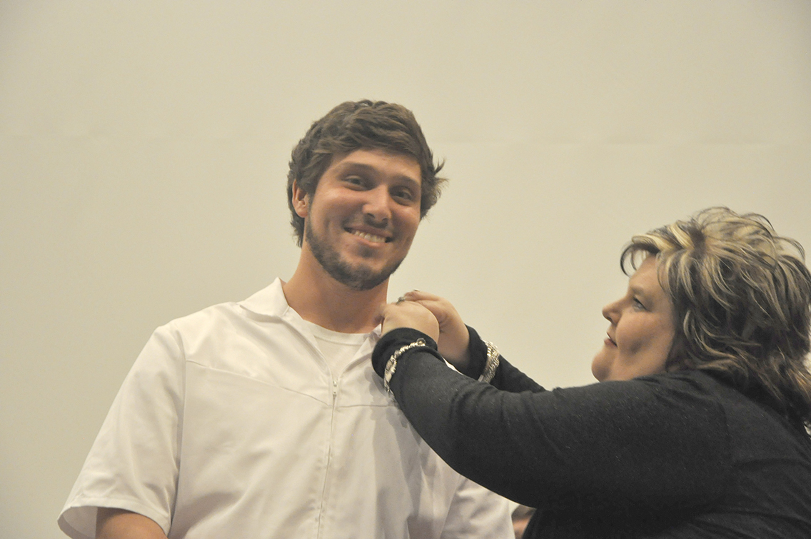 J.B. Laxton (left) of Munford received his nursing pin from Dean of Nursing Amy Johnson (right) during DSCC's Nursing Pinning Ceremony Dec. 9.