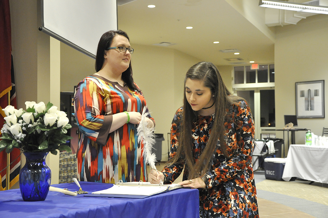 PTK Inductee Brianna Burse of Halls (right) signs her name on the ledger during DSCC's 2017 Induction Ceremony March 17. Also shown is PTK member Rachel Isaak of Gates (left).