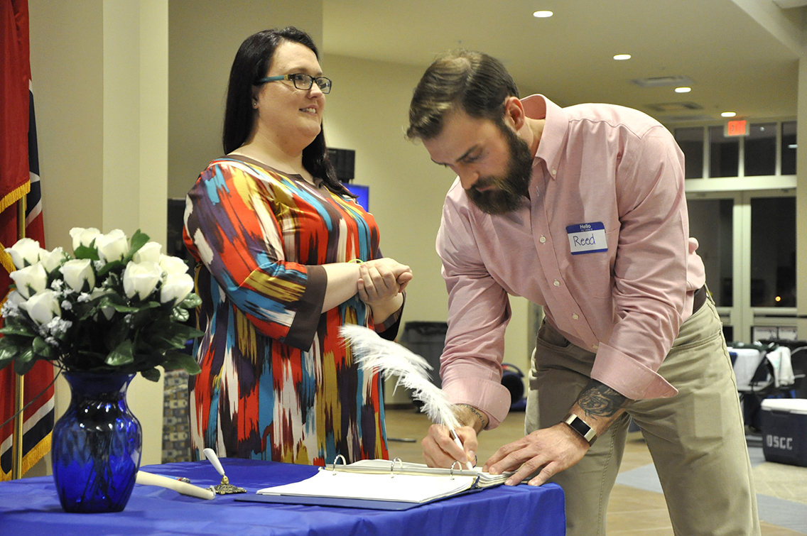 PTK Inductee Reed Daniels of Dyersburg (right) signs his name on the ledger during DSCC's 2017 Induction Ceremony March 17. Also shown is PTK member Rachel Isaak of Gates (left).