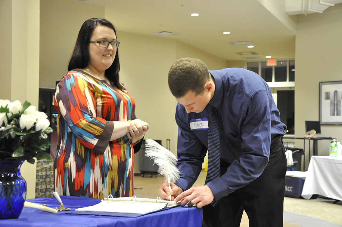 PTK Inductee Isaac Mecklin of Munford (right) signs his name on the ledger during DSCC's 2017 Induction Ceremony March 17. Also shown is PTK member Rachel Isaak of Gates (left).