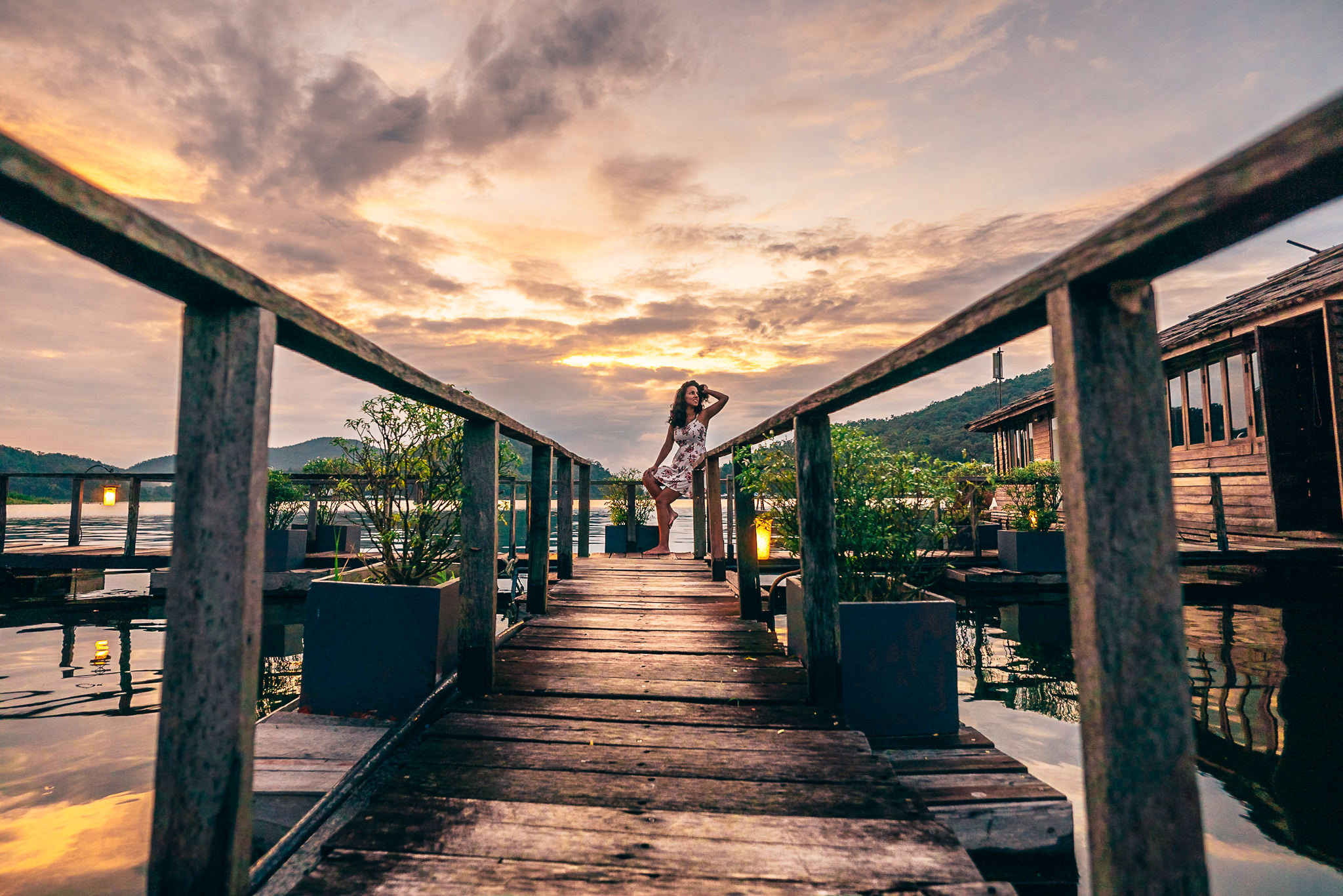 After placing Marta in front of this sunset near Chiang Mai, I noticed the wooden rails could be used as leading lines to direct attention towards her (considering how small she is in the frame), so I lowered myself to the ground to get the appropriate perspective.