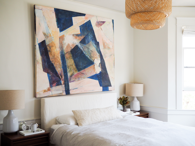 Slipcovered Parsons bed: via  Restoration Hardware warehouse sale.Pink and navy abstract art, original: similar .Linen duvet in fog: Parachute . White sheets:  Brooklinen . Cream lumbar pillow, handmade: similar . Rattan pendant:  Ikea .