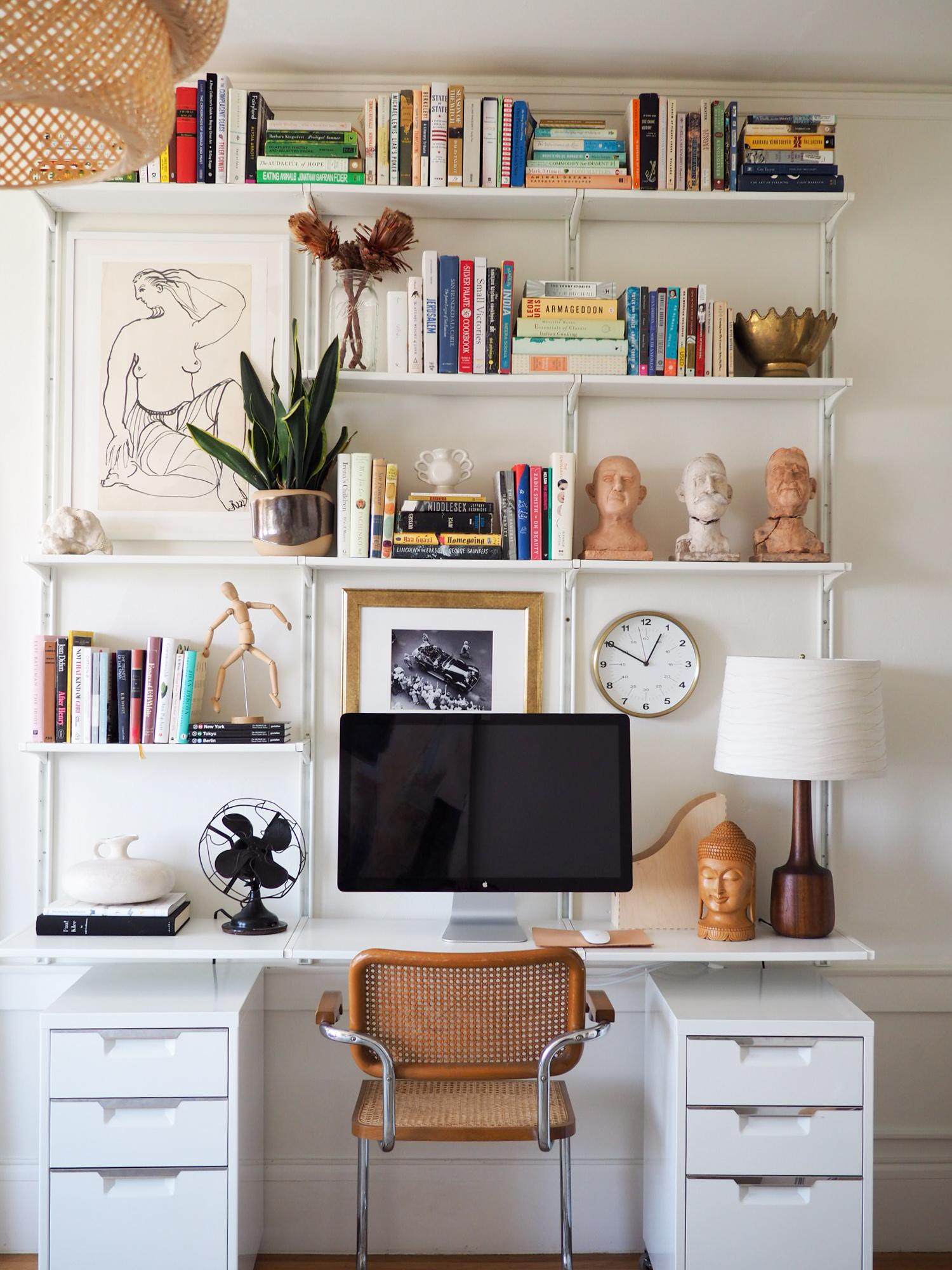 Figure drawing, vintage:  similar . White frame:  Ikea . Marcel Bruer-style desk chair, via Craigslist:  similar . White file cabinets, via Craigslist:  CB2 . Wall shelving:  Ikea .Brass wall clock:  Target . Gold picture frame:  Ikea . Leather mousepad:  Etsy .Walnut mid-century lamp base, vintage via eBay:  similar . Cream woven lamp shade:  Target .