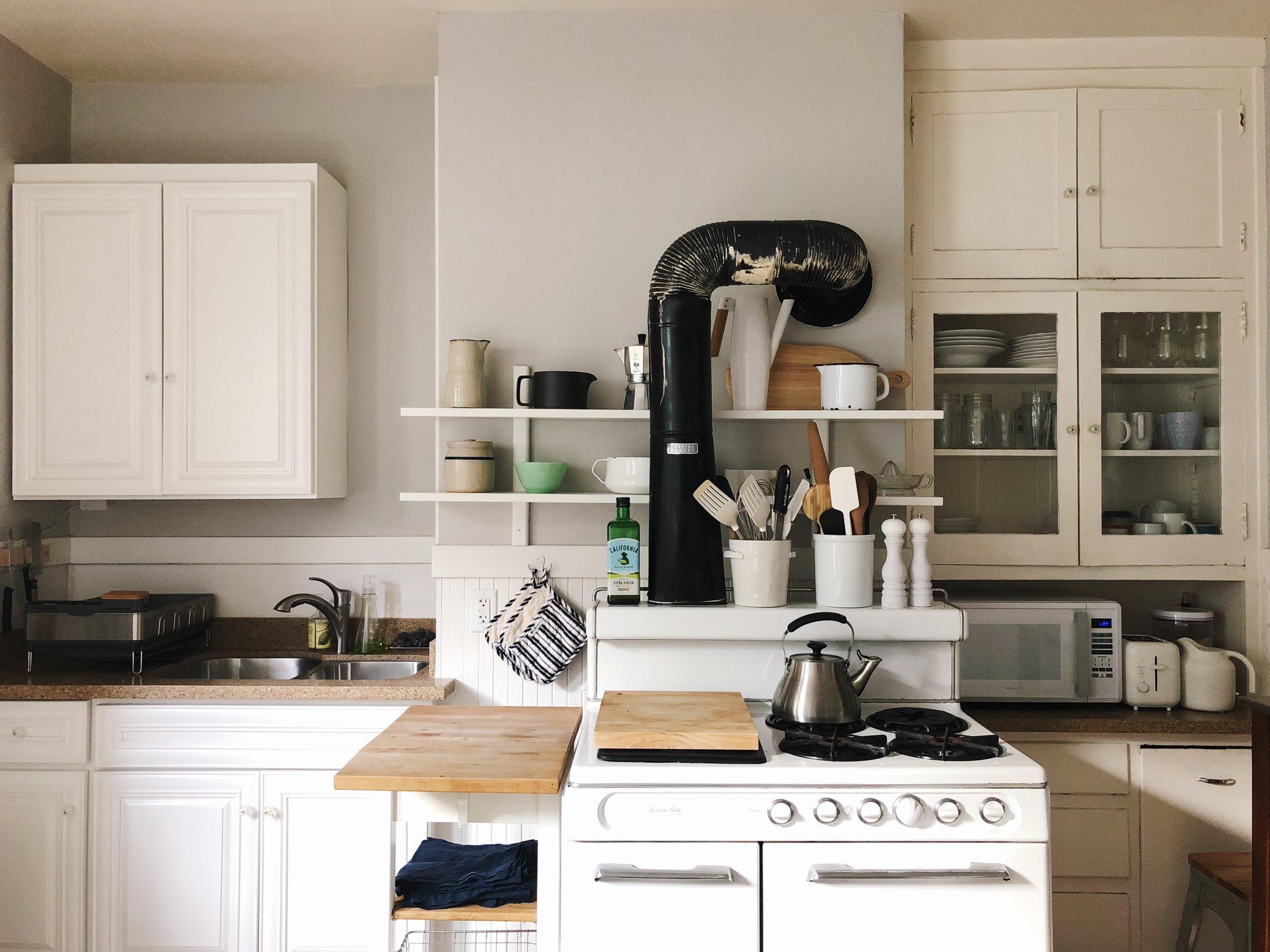 Kitchen cart:  Ikea . White wall shelves: Ikea. Pot holders:  Williams Sonoma . Navy napkins:  Crate and Barrel . Dish rack:  SimpleHuman .