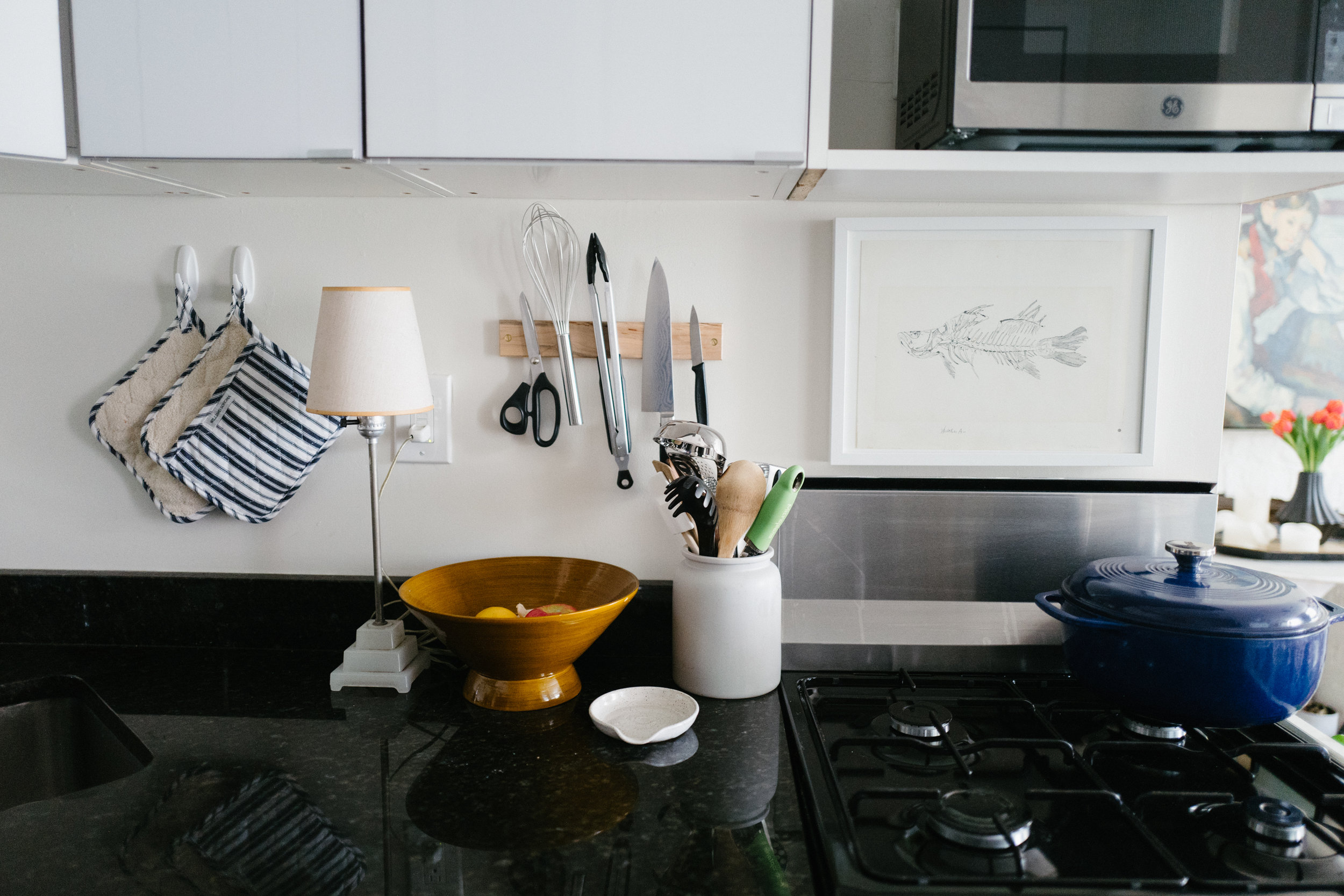 Blue dutch oven:  Amazon . Lamp: vintage. Magnetic knife strip:  Benchcrafted . Utensil holder:  CB2 . Spoon rest:  Schoolhouse Electric . Fish print: Vintage. Pot holders:  Williams Sonoma .