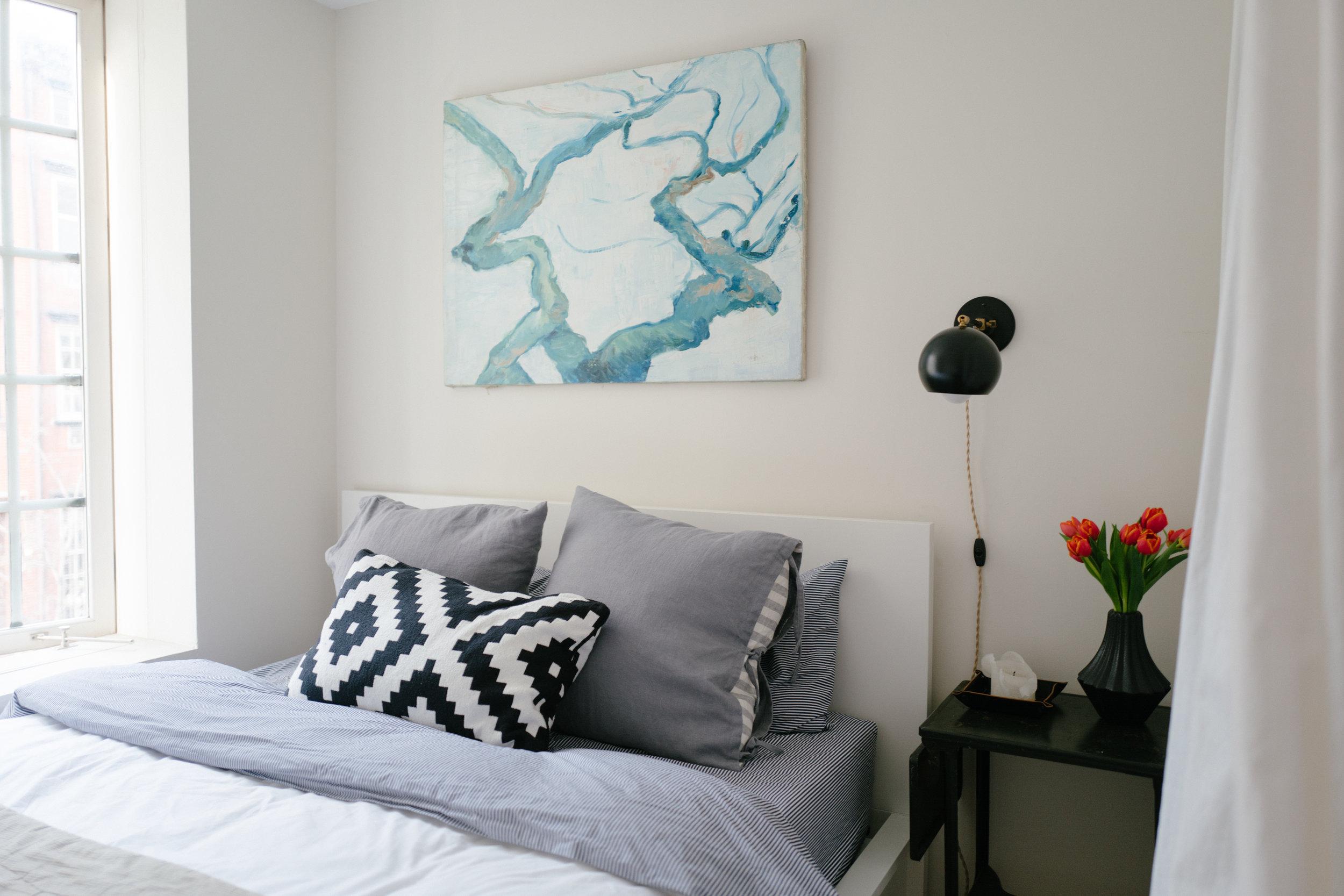Wall sconce:  Schoolhouse Electric . Bed:  Ikea . Bedding:  Brooklinen . Black table: Vintage,  similar . Black vase:  CB2 . Shams:  Ikea .