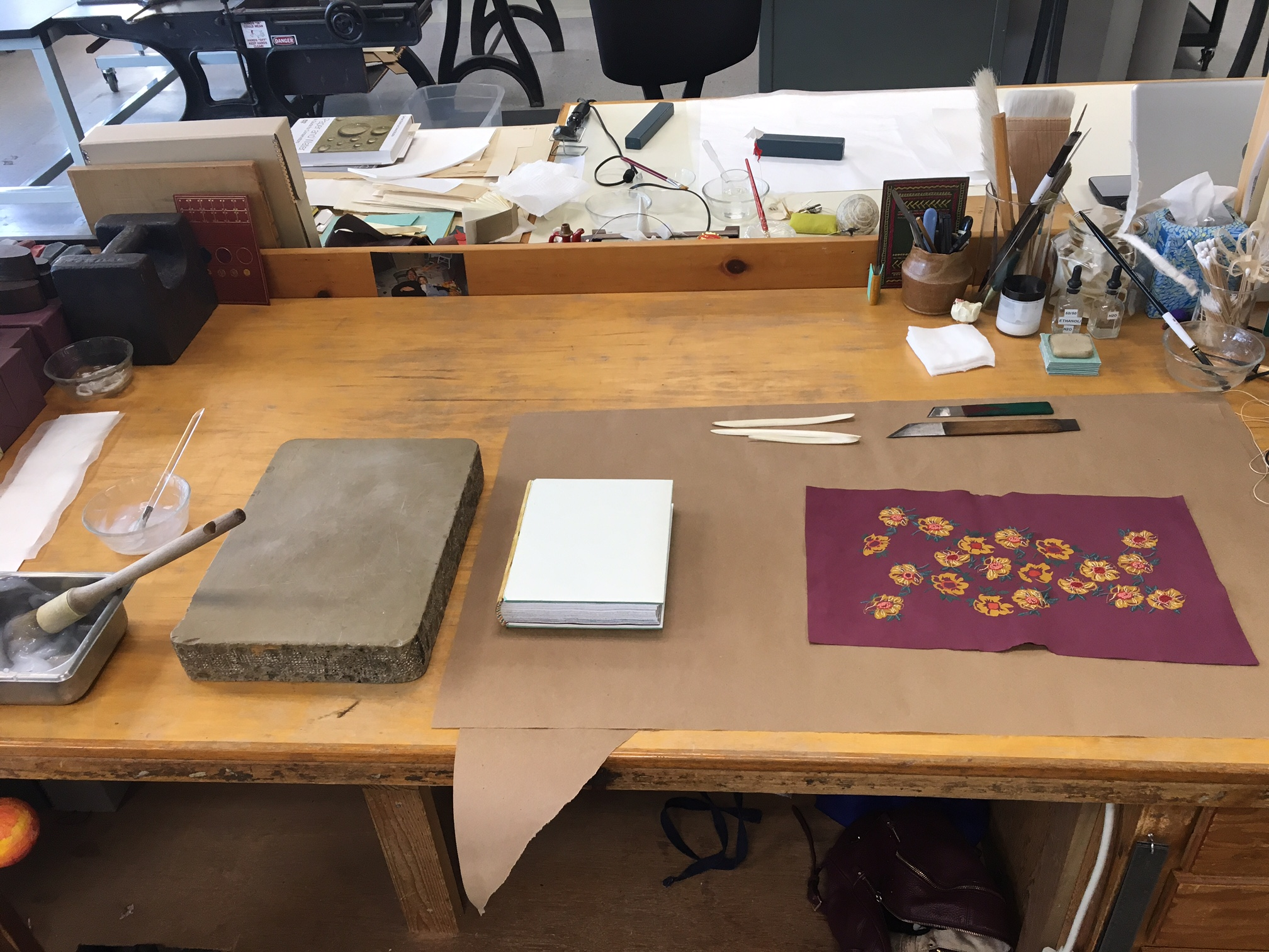My bench set up before covering. You can see my paste, a litho stone, the binding (which I still had to cap up!), a few bone folders useful for forming headcaps and corners, paring knives, and the covering skin.