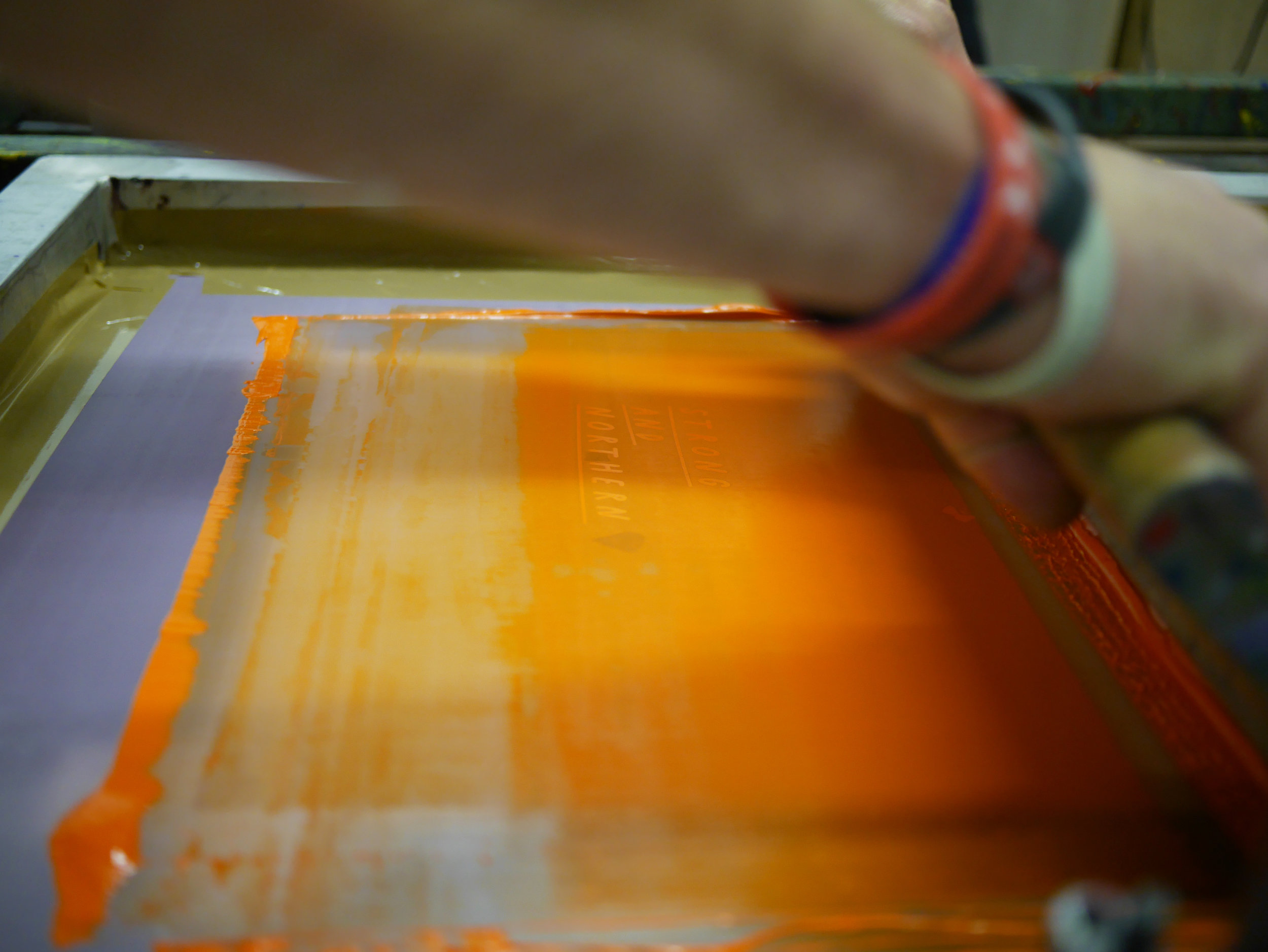 A close up of James screen printing our Strong and Northern design.