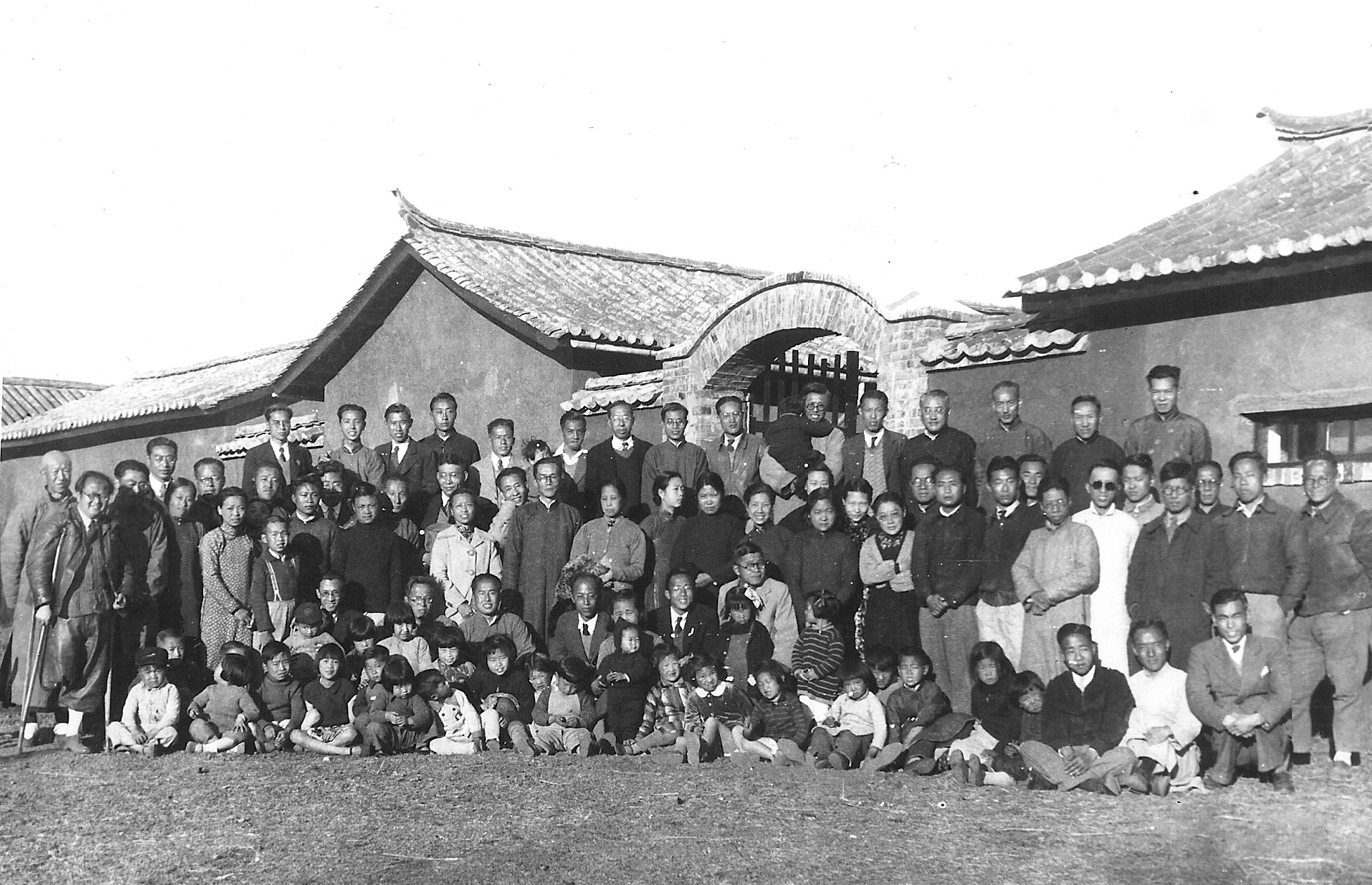 Group photo of faculty and family of National Southwest Associated University (Xinan Lianda), 1940. CK Jen is at the center front row, kneeling down, with his wife,Paocheng Tao, on his right side, her face partly obscured by a standing May, their first-born daughter. Image courtesy George Koo.